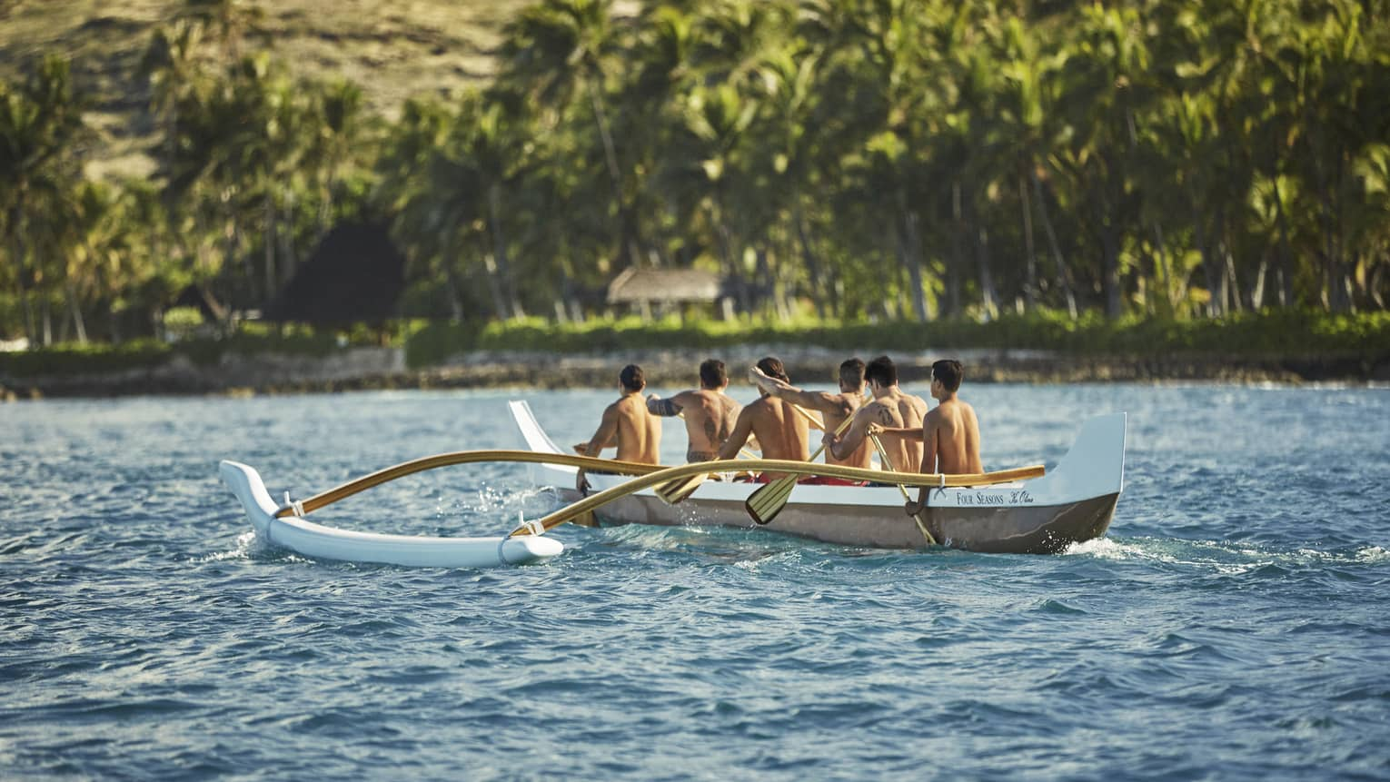 Guests paddling through clear water on a specialized boat in Oahu