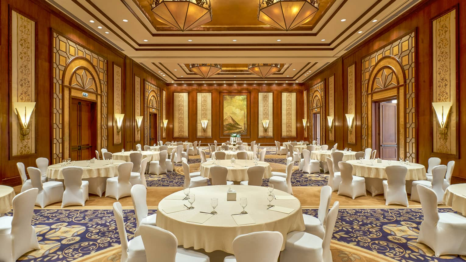 Tiran Ballroom with large white banquet tables, chairs under gold and wood Art Deco style lights, walls