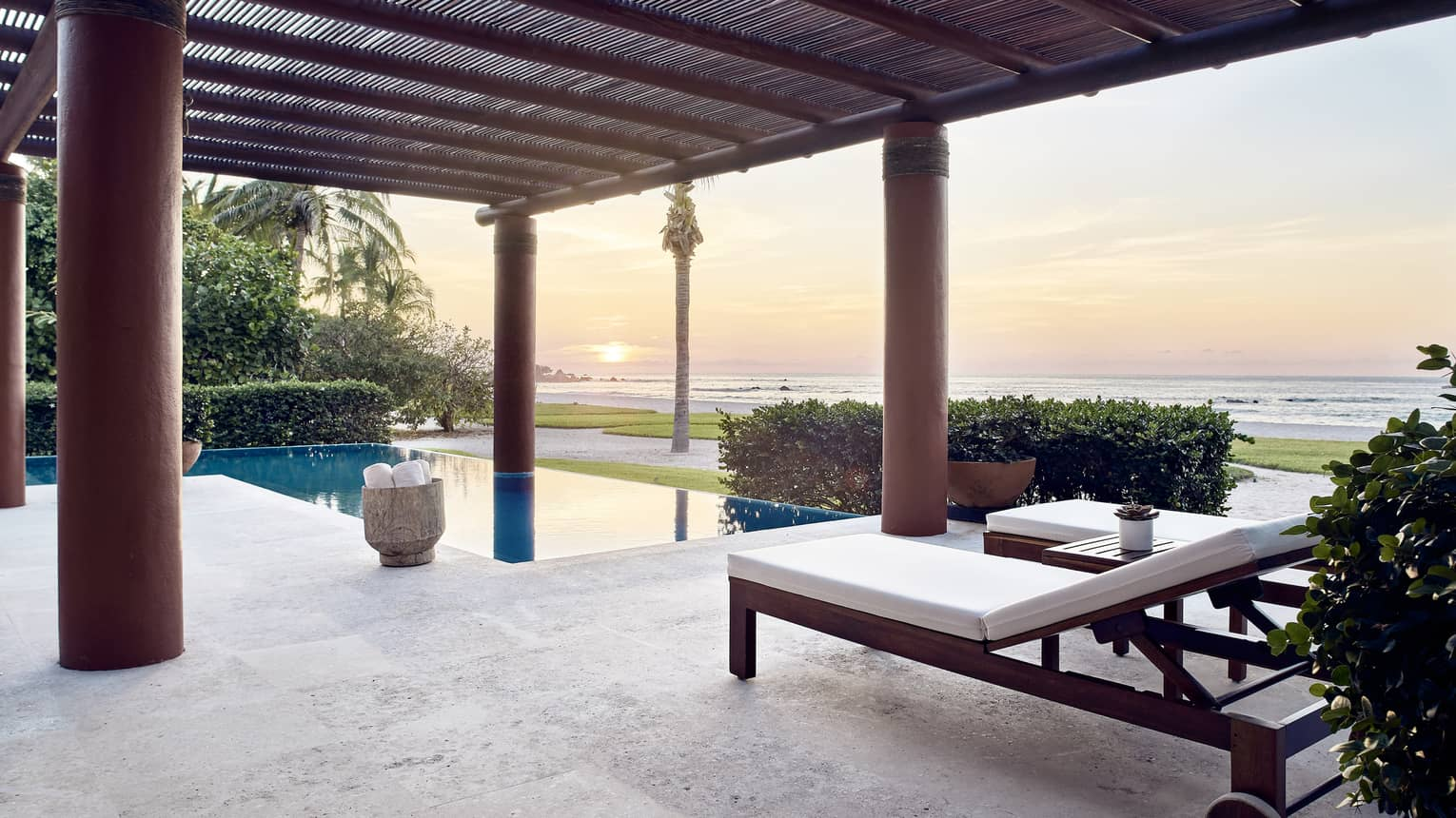 Outdoor terrace with lounge chairs, private pool, sun setting over the sea