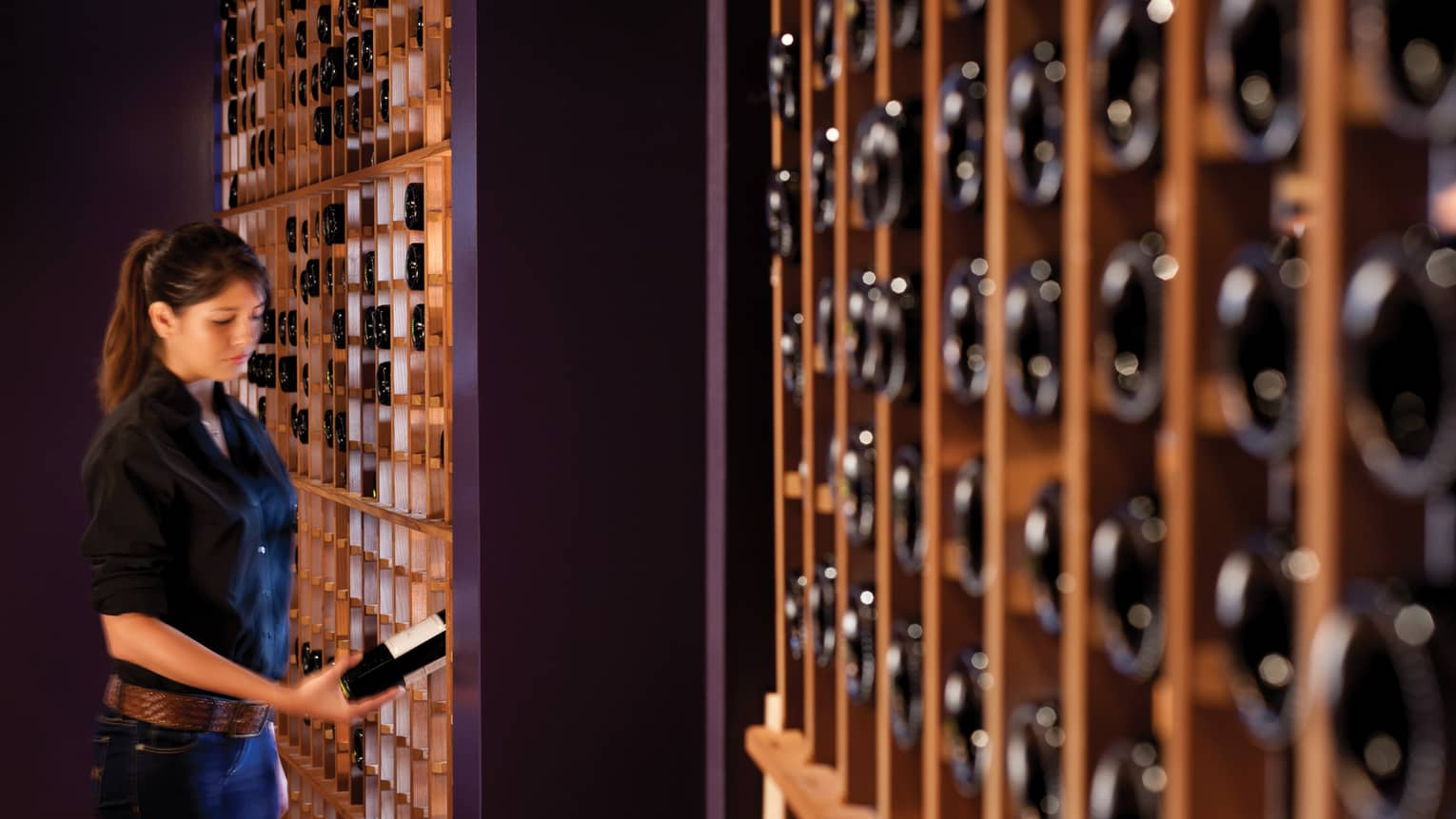 Woman in black button-up shirt and jeans retrieves a wine bottle from cellar rack