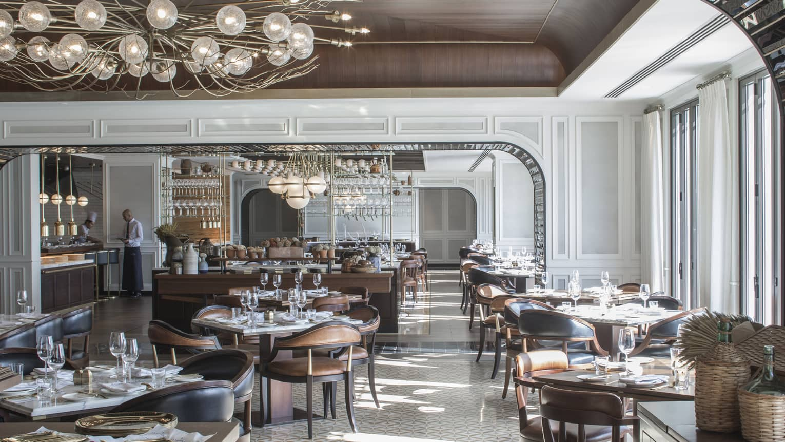 Large, sunny La Capitale dining room with elegant brown leather chairs, tables, white tile, modern chandeliers, server at counter