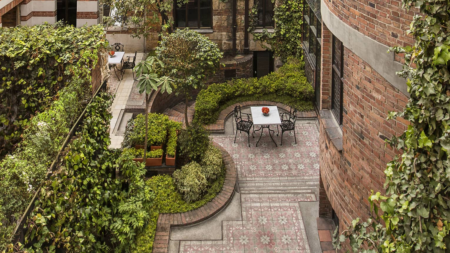 Aerial view of wrought-iron patio tables and chairs in brick courtyard, trees and shrubs throughout