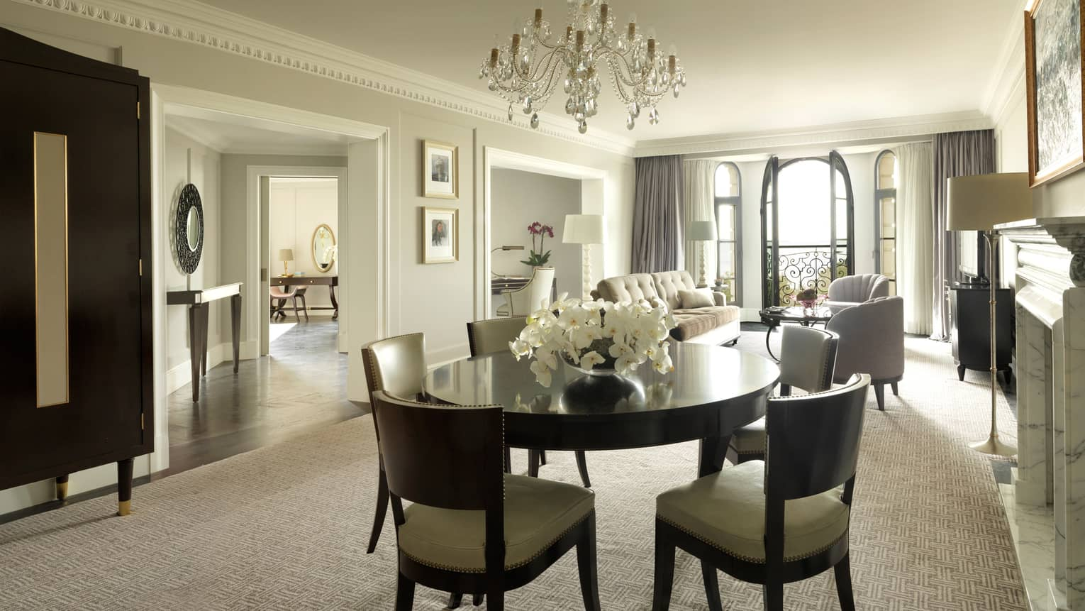 One-bedroom Suite round dining room table for 6, small crystal chandelier, living room, French doors to balcony in background