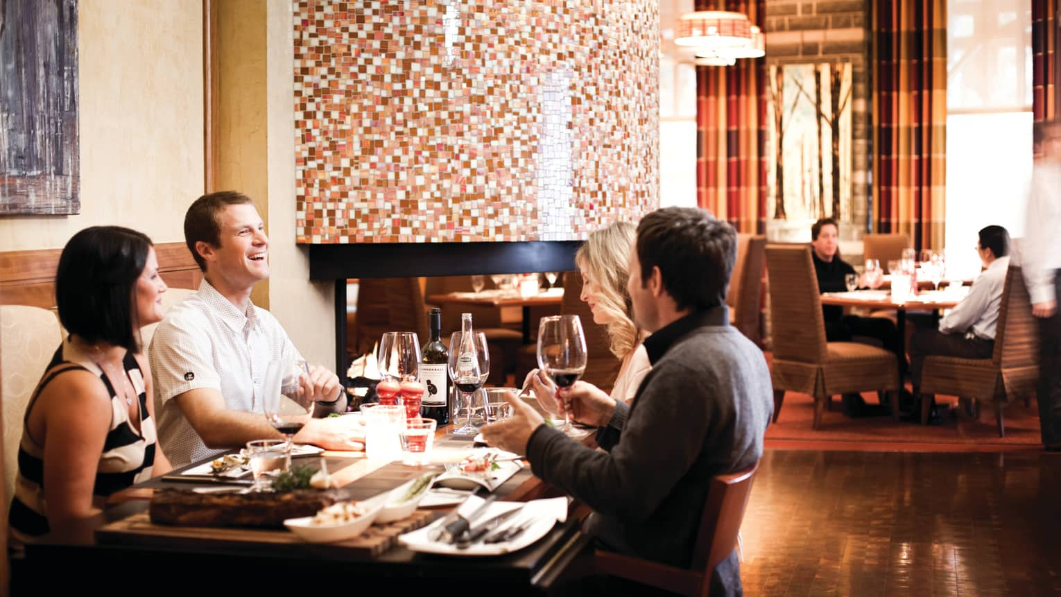Four friends laugh over dinner, wine at table in Sidecut restaurant dining room
