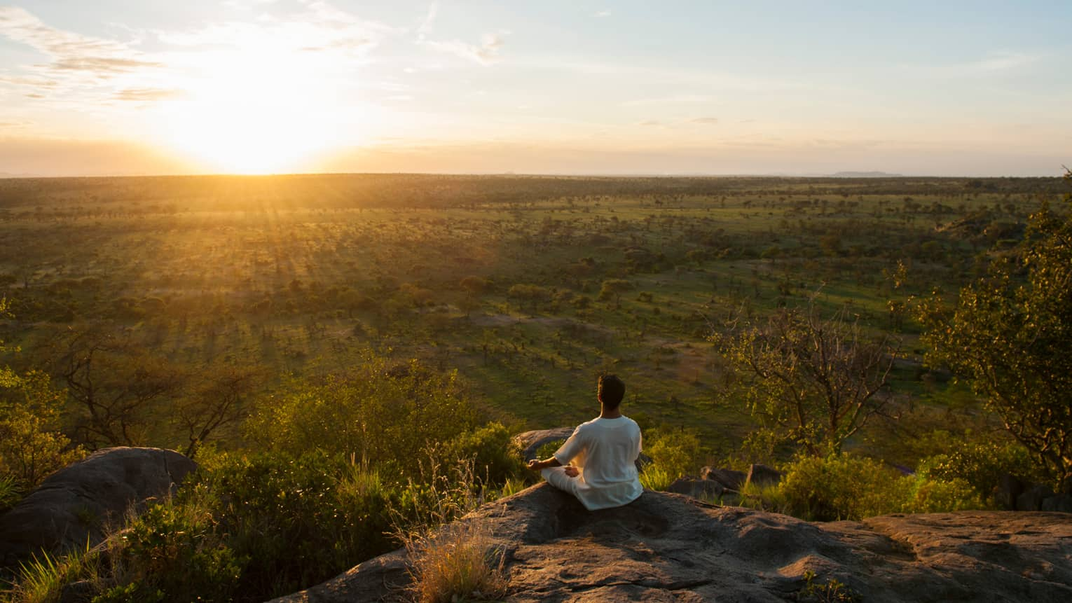 Woman sits crossed-legged, meditates on cliff overlooking Serengeti sunset