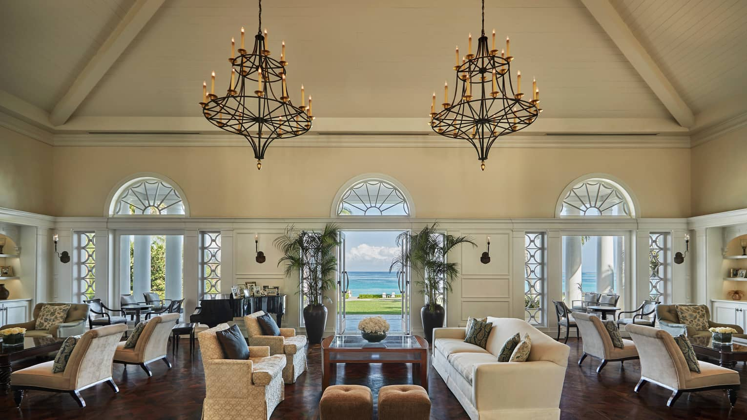Large iron chandeliers hang from cathedral ceilings over sofas, arched windows in lobby