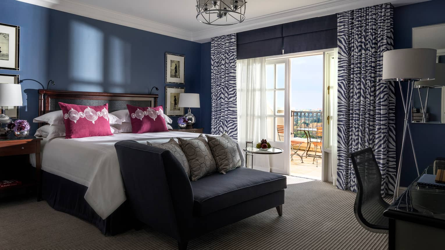 Hotel room with navy walls, white bed and magenta pillows, black settee at foot, zebra curtains by french doors