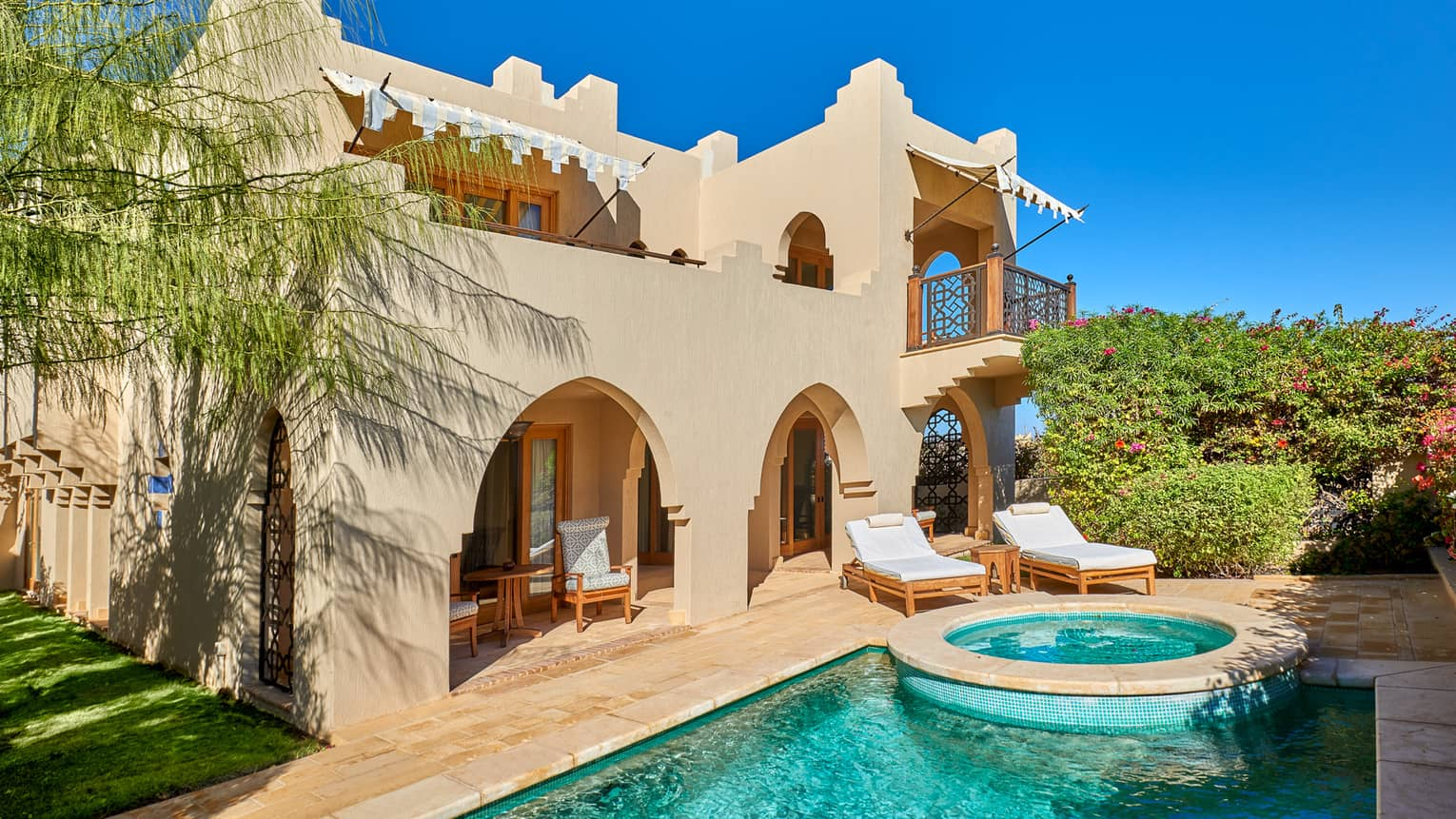 Exterior view of four bedroom villa and private pool against blue sky