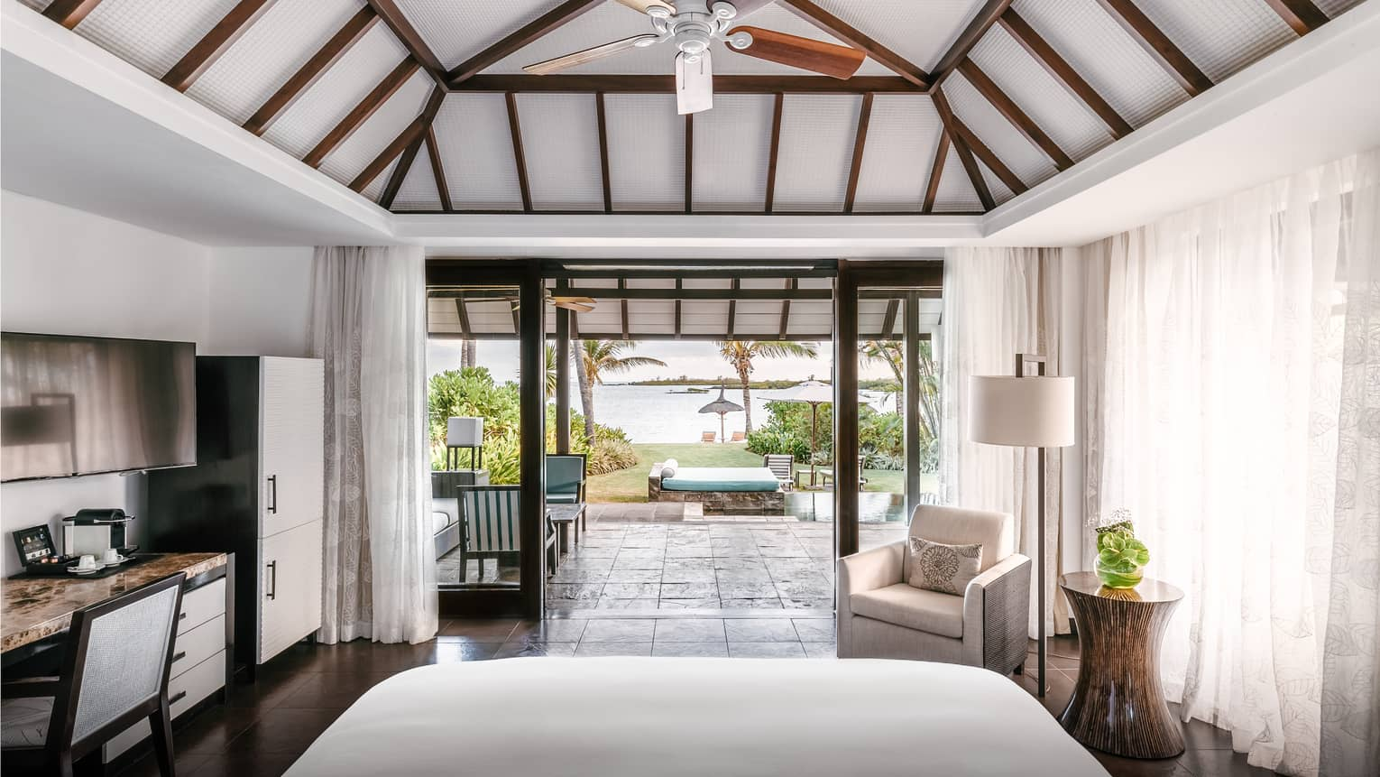 One-bedroom villa with vaulted white and wood-beamed ceiling, white bed and views out to lagoon