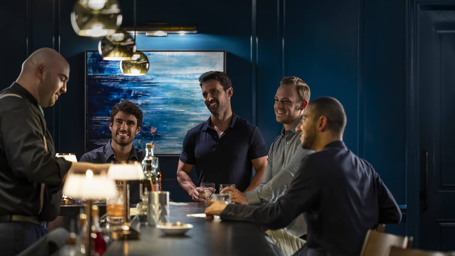 A group of men watch the bartender pour a drink
