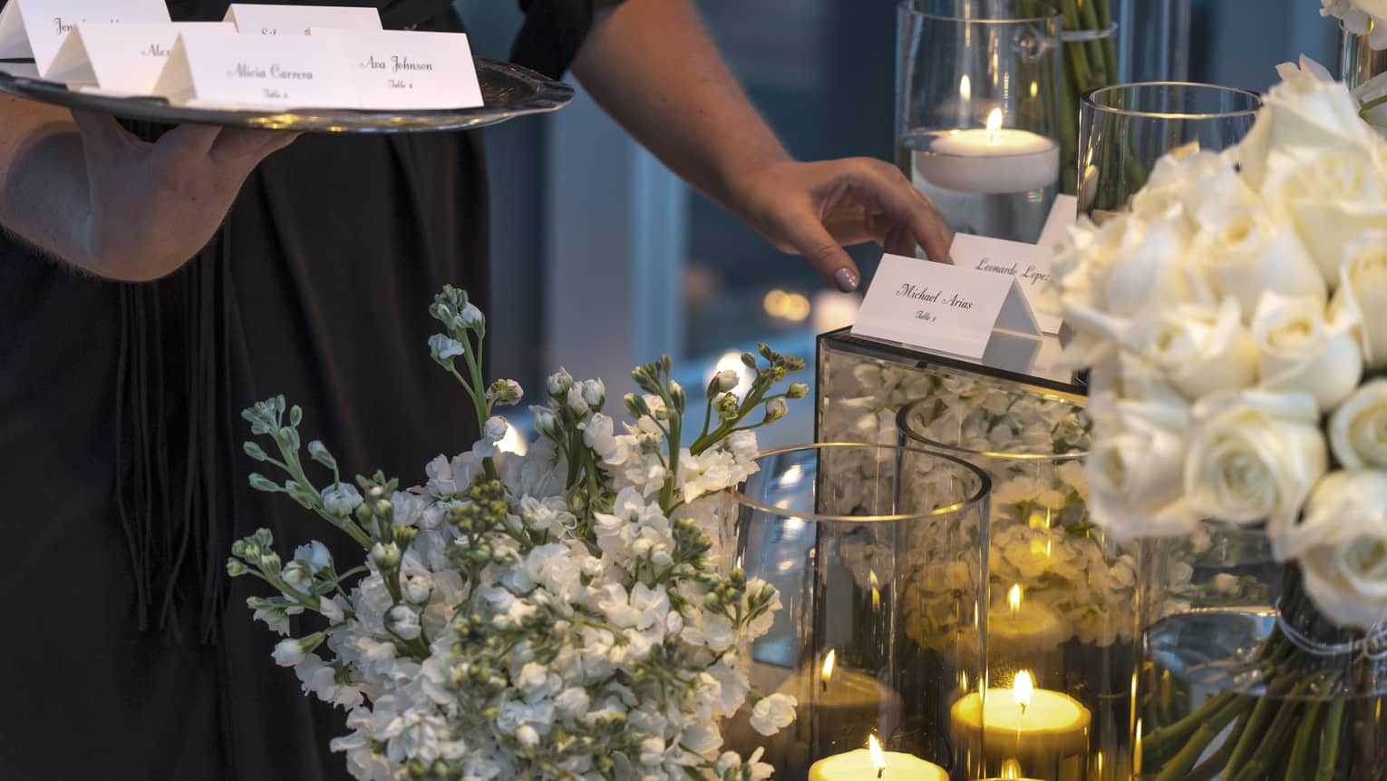 Event staff with tray places name cards on elegant banquet table with white flowers, candles