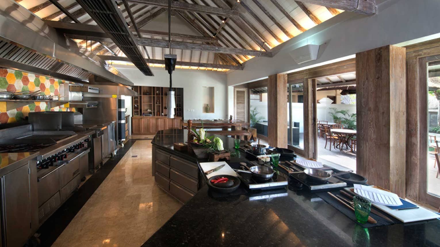 Jimbaran Bay Cooking Academy kitchen with stainless steel appliances, black marble counters, large windows