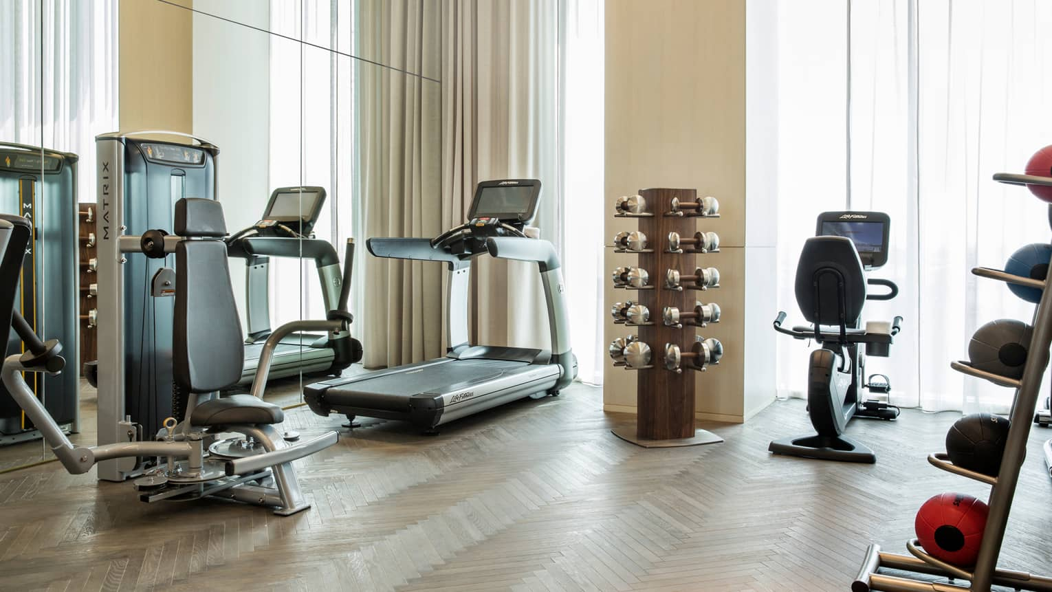 Cardio exercise machines, rack of hand weights near windows with long curtains in fitness centre