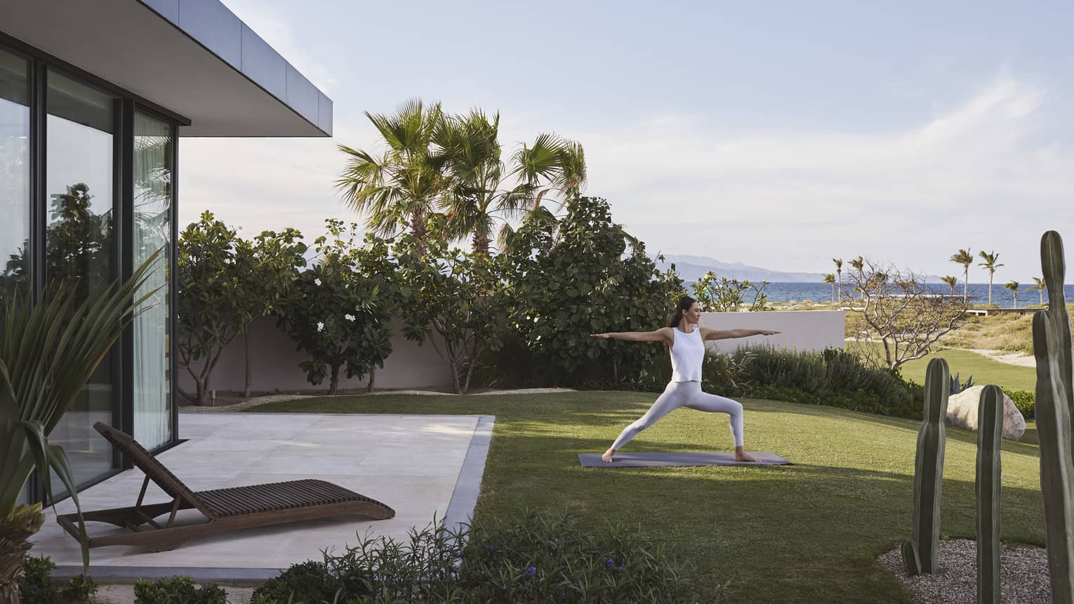 Woman doing yoga on a lawn outside her suite, with the ocean and sky in the background.