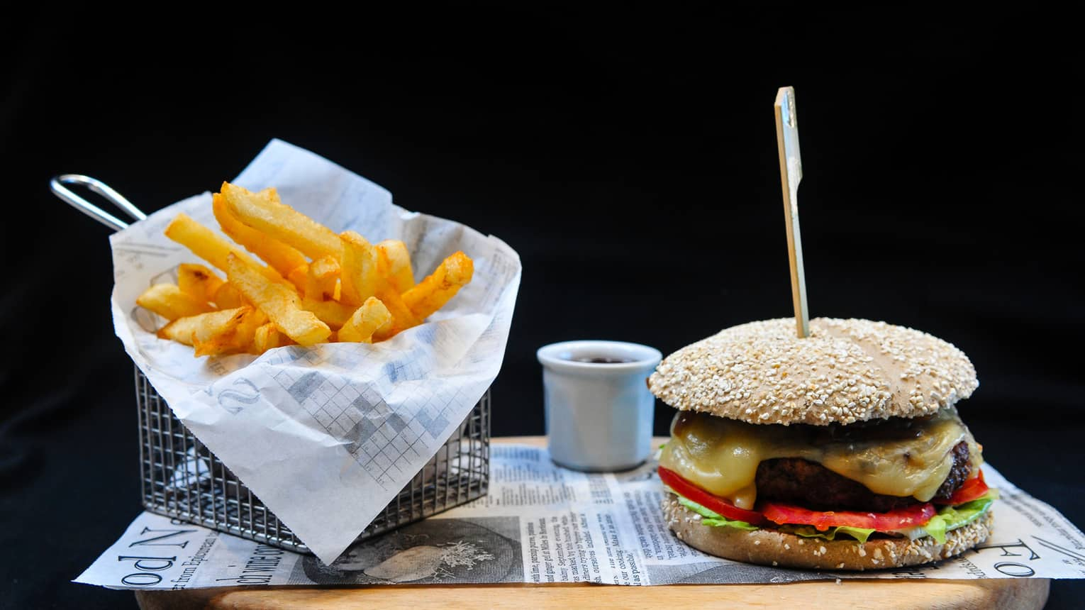 A burger with lettuce, tomato and cheese sits on a tray next to a basket of french fries