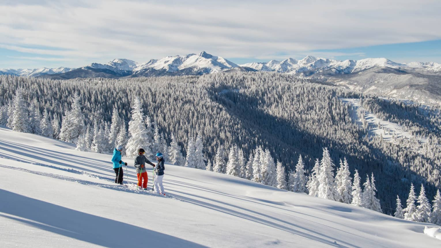 Three guests on skis pause on the ski hill, snow capped trees and mountains in distance