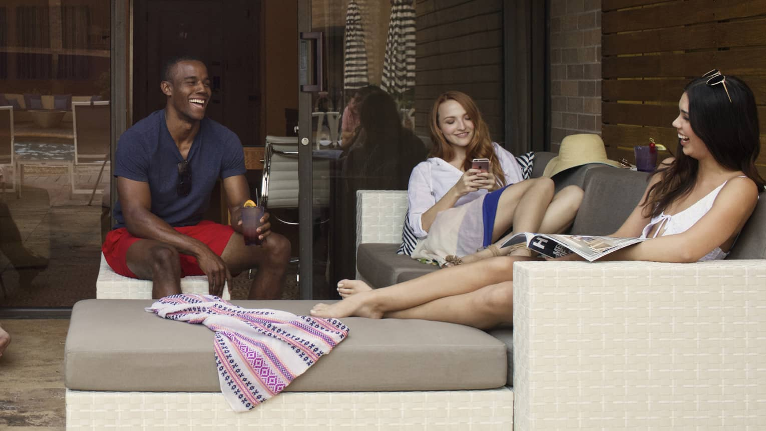 A man and two women laugh on a tan outdoor poolside sectional at four seasons hotel houston