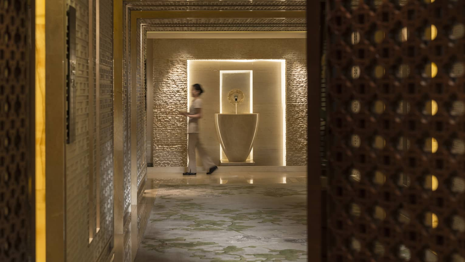 Spa staff walks with towels down marble hall past tall vase