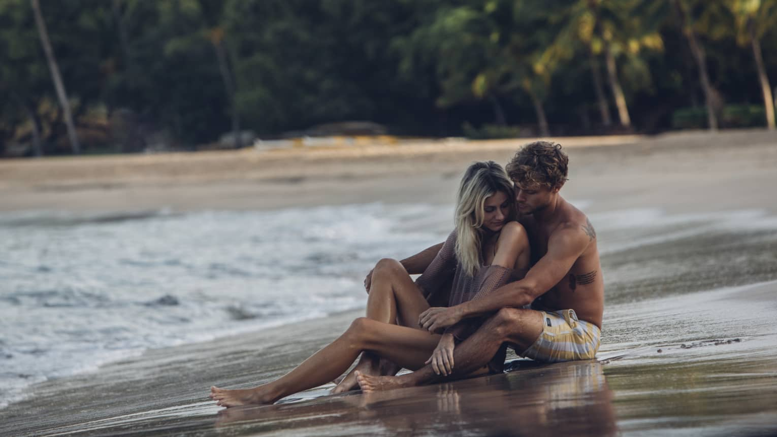 A couple embrace each other on a beach