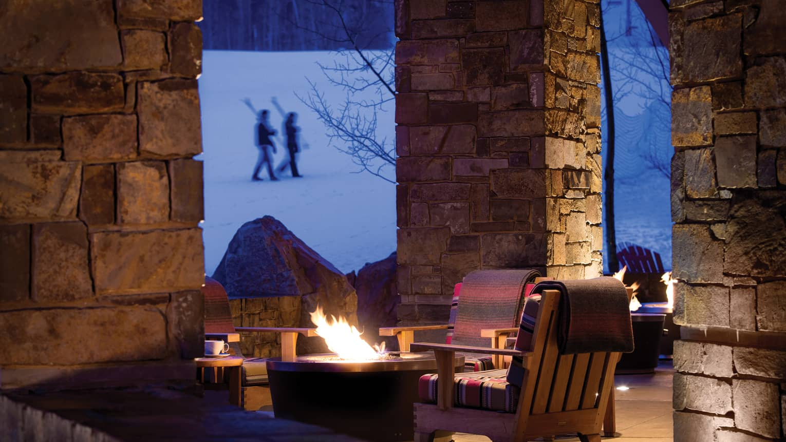 Large wood patio chairs around outdoor gas fire pits by stone columns, skiers walk on hill in background