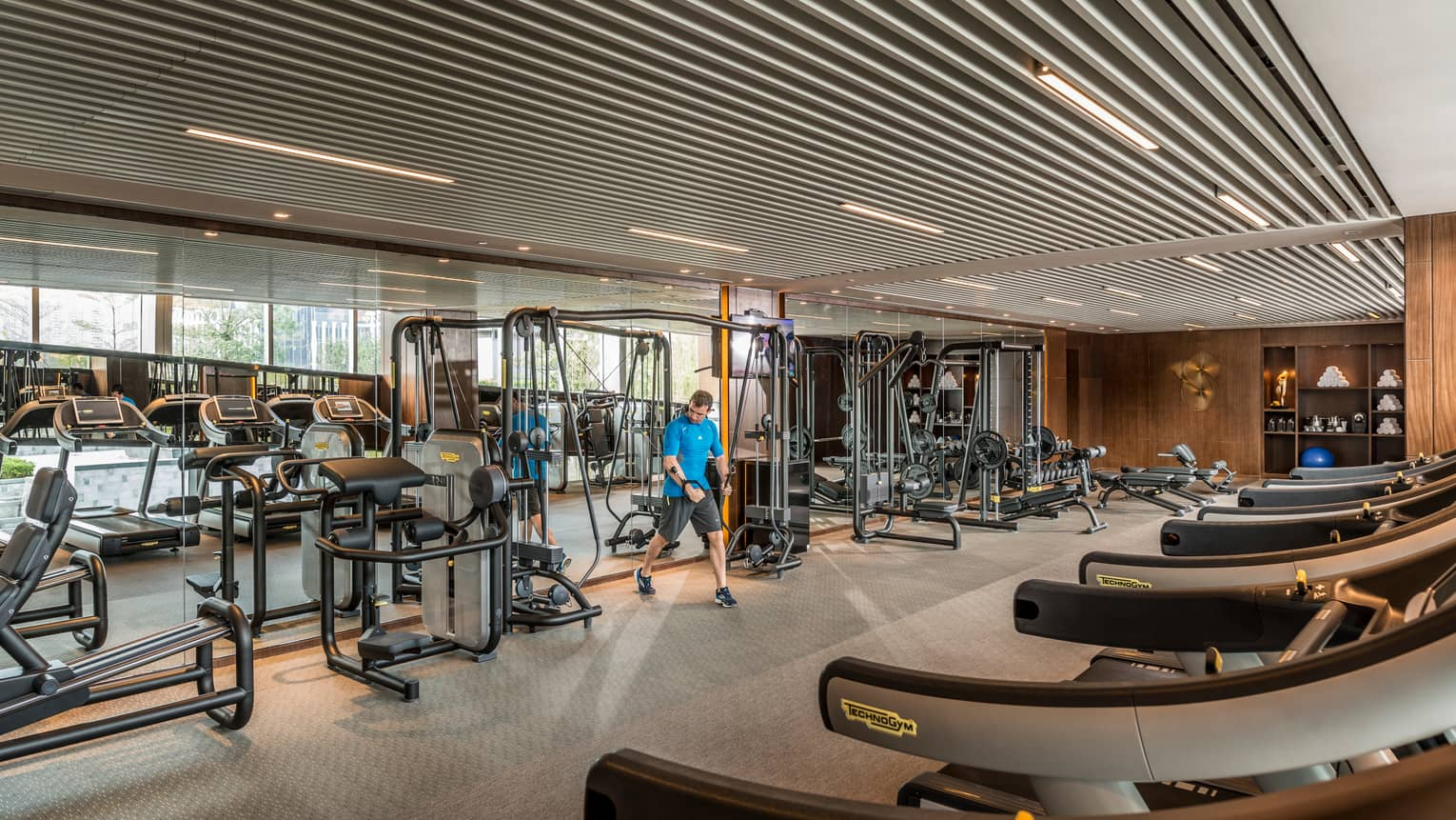 Man pulls weights machine in large Fitness Centre by mirror reflecting treadmills