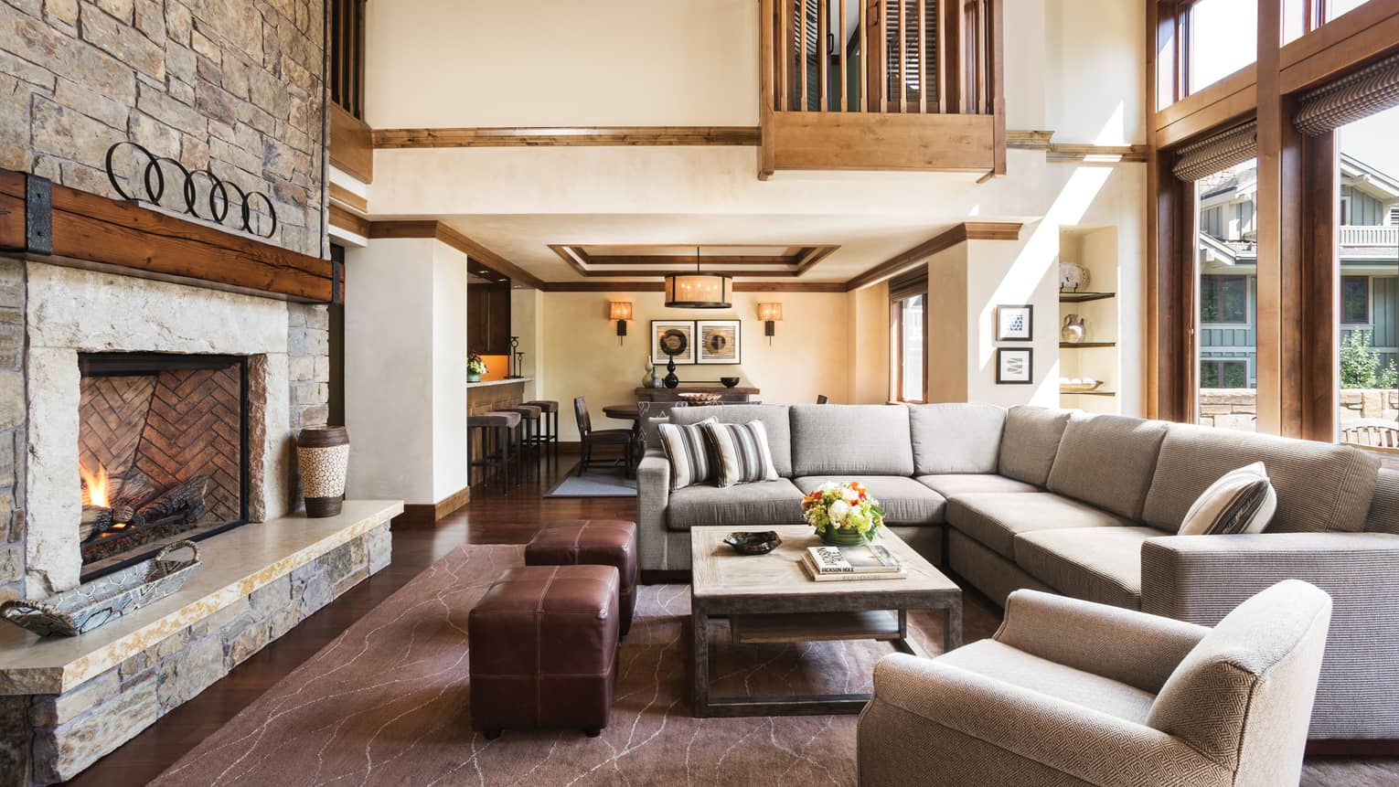 Large L-shaped sofa, ottomans by fireplace under large loft ceilings, wood balconies