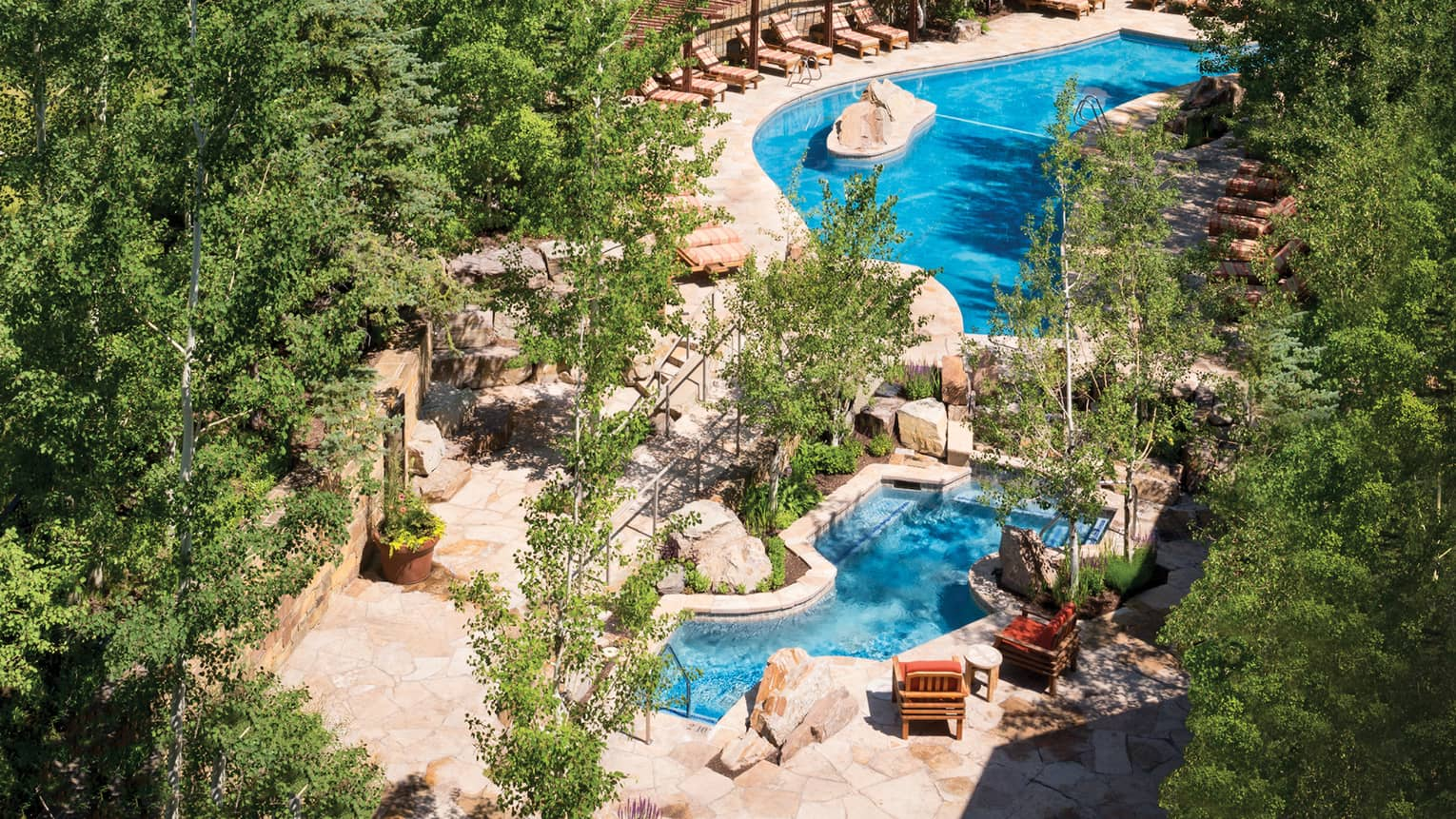 Aerial view of winding outdoor swimming pool, deck with lounge chairs surrounded by trees
