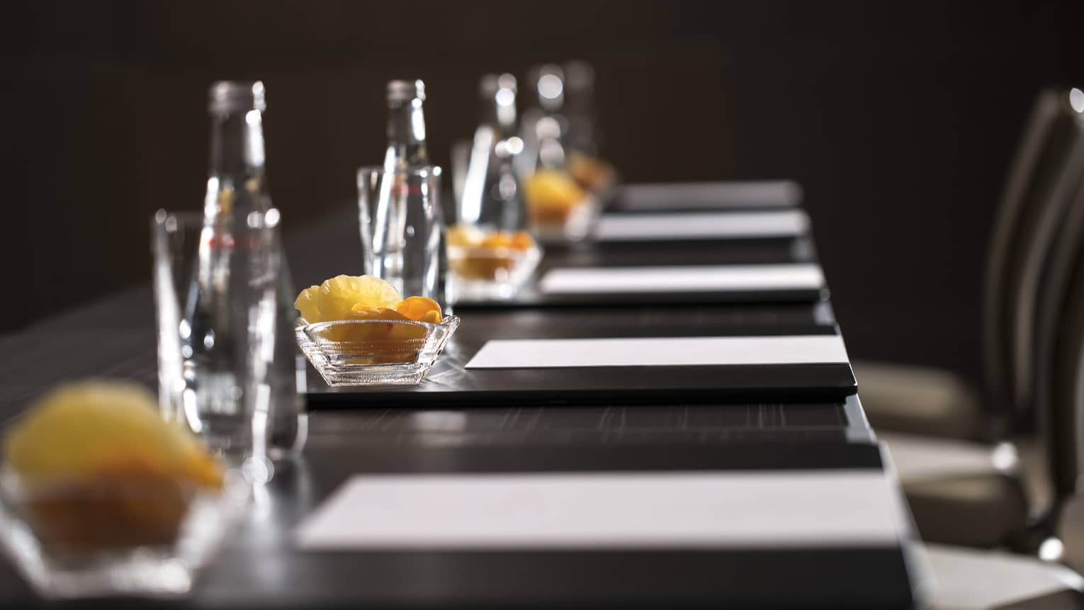 Row of glass bottles, small dishes with dried fruits, meeting agendas along boardroom table