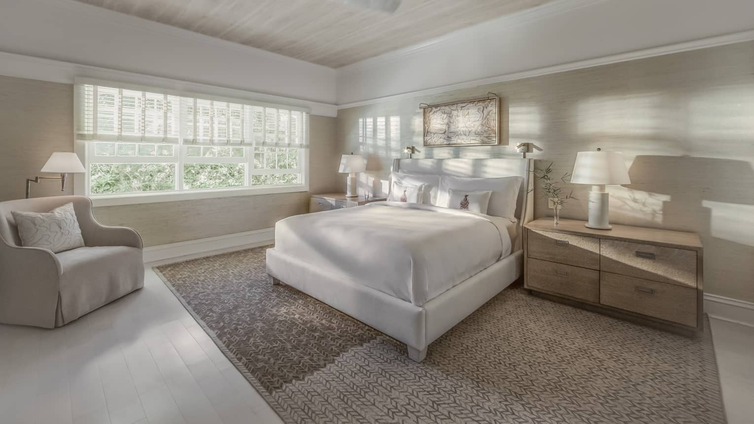 Sunlight and shadows shine through the window of a master suite bedroom