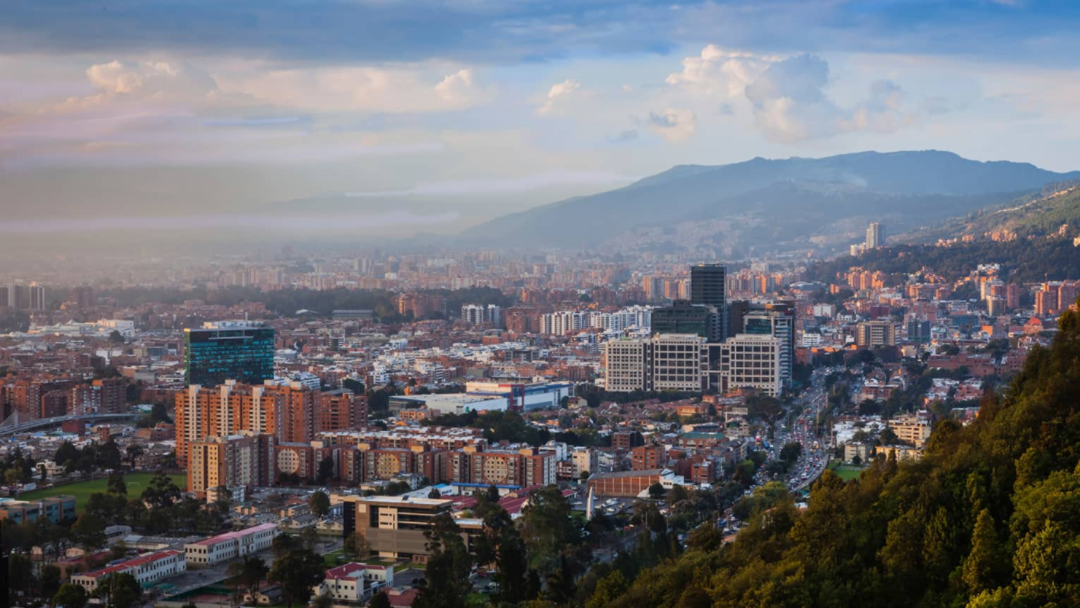 Aerial view of Bogota city, buildings and houses below misty mountains