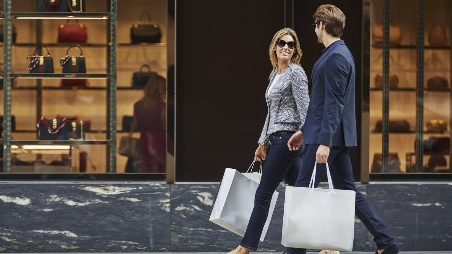 Man and woman walk down street, carry large paper shopping bags