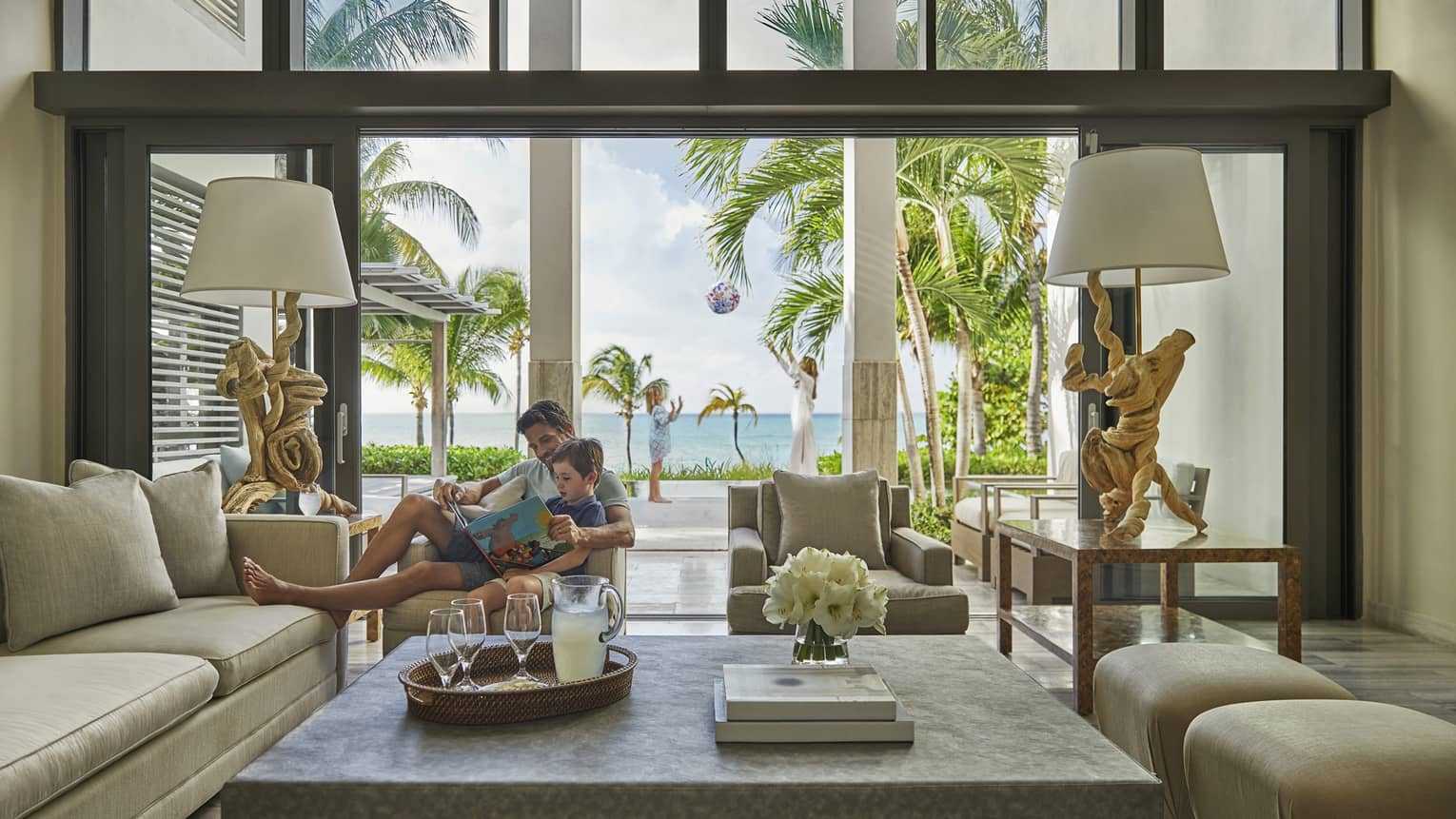 A father reading to his son in a luxurious living room leading out onto a terrace with the ocean and palm trees beyond.