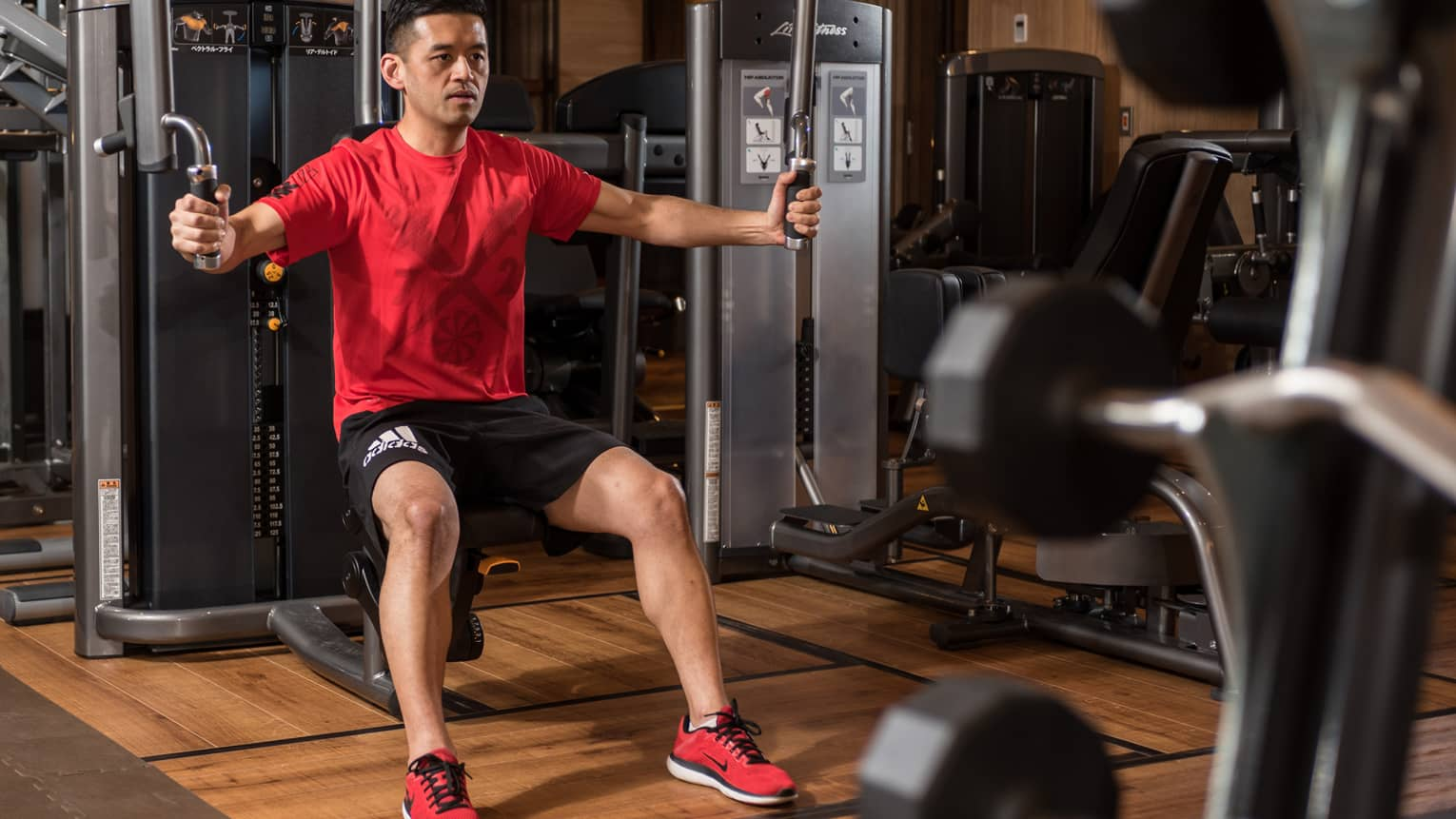 Man in red shirt sits on bench, prepares to pull weights in Fitness Centre