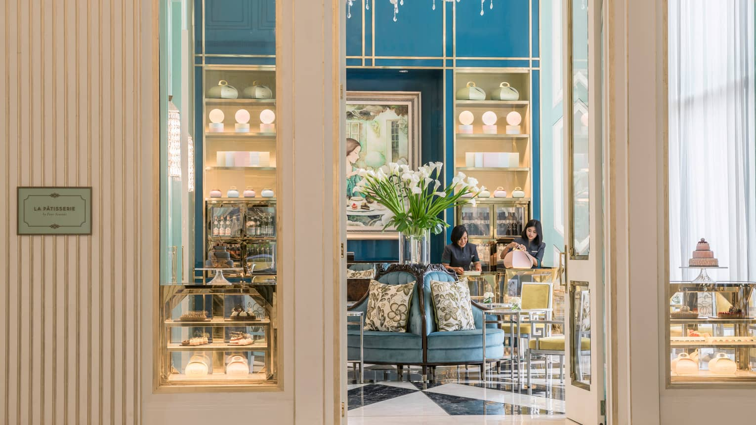 View inside La Patisserie doors with elegant blue and gold chairs, tall glass vase with white flowers, woman fastening pink box