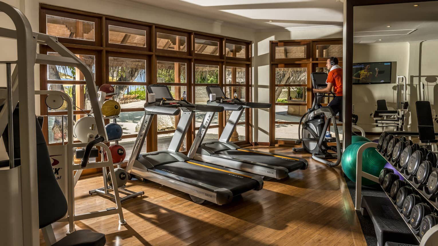 Gym with wooden floors, two treadmills, person on elliptical, free wights, windows looking out to beach