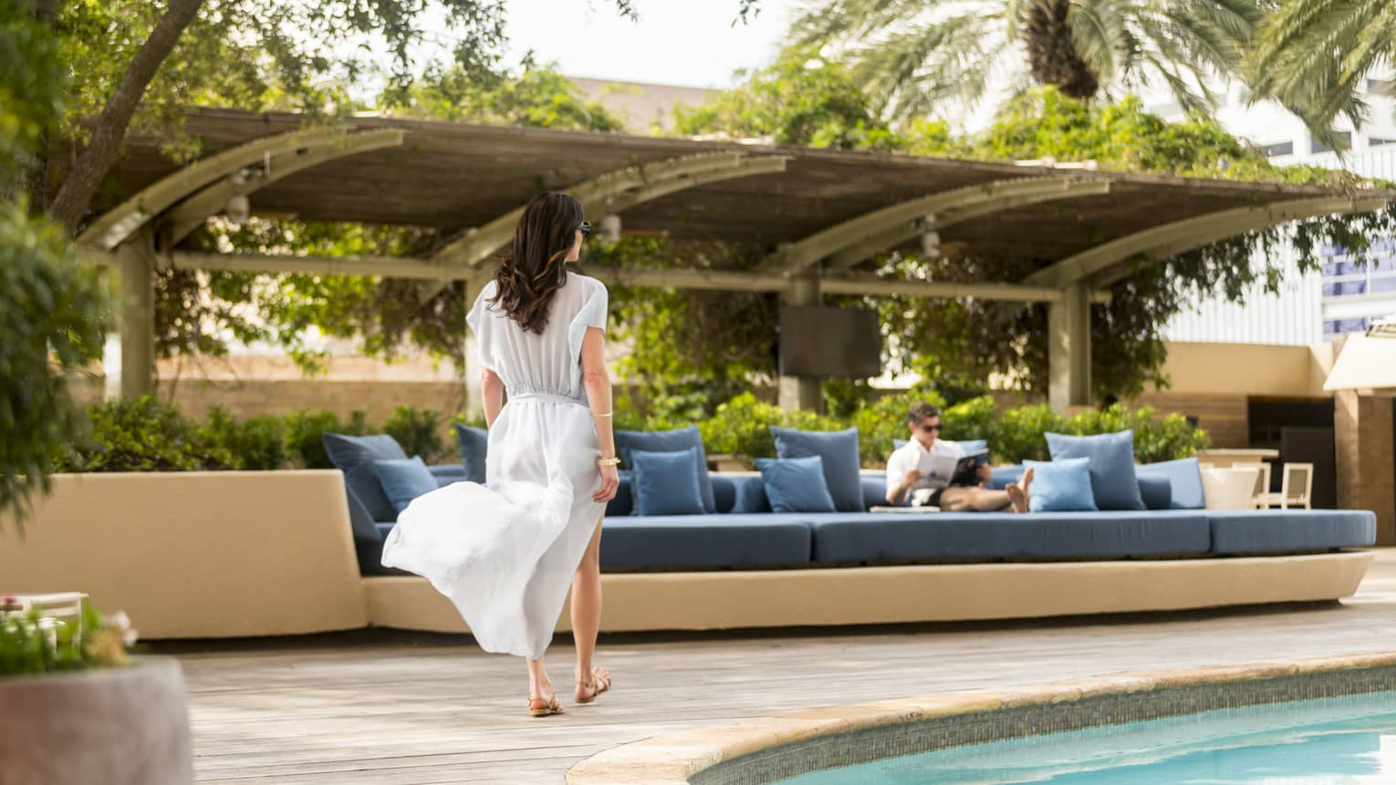 Woman in white flowing dress walks by swimming pool to blue banquette where man is reading magazine