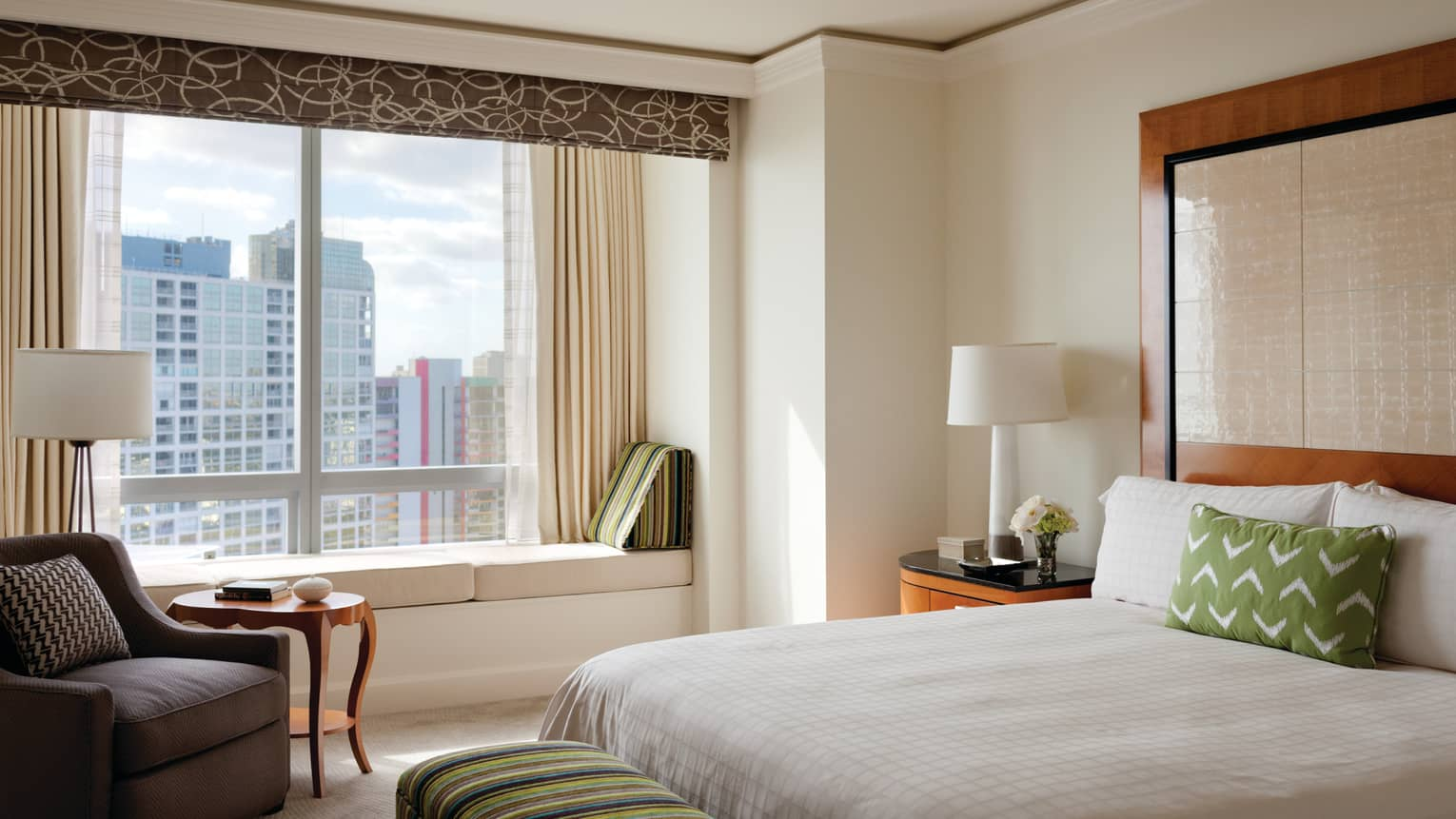 A hotel room with an open window looking out at the city
