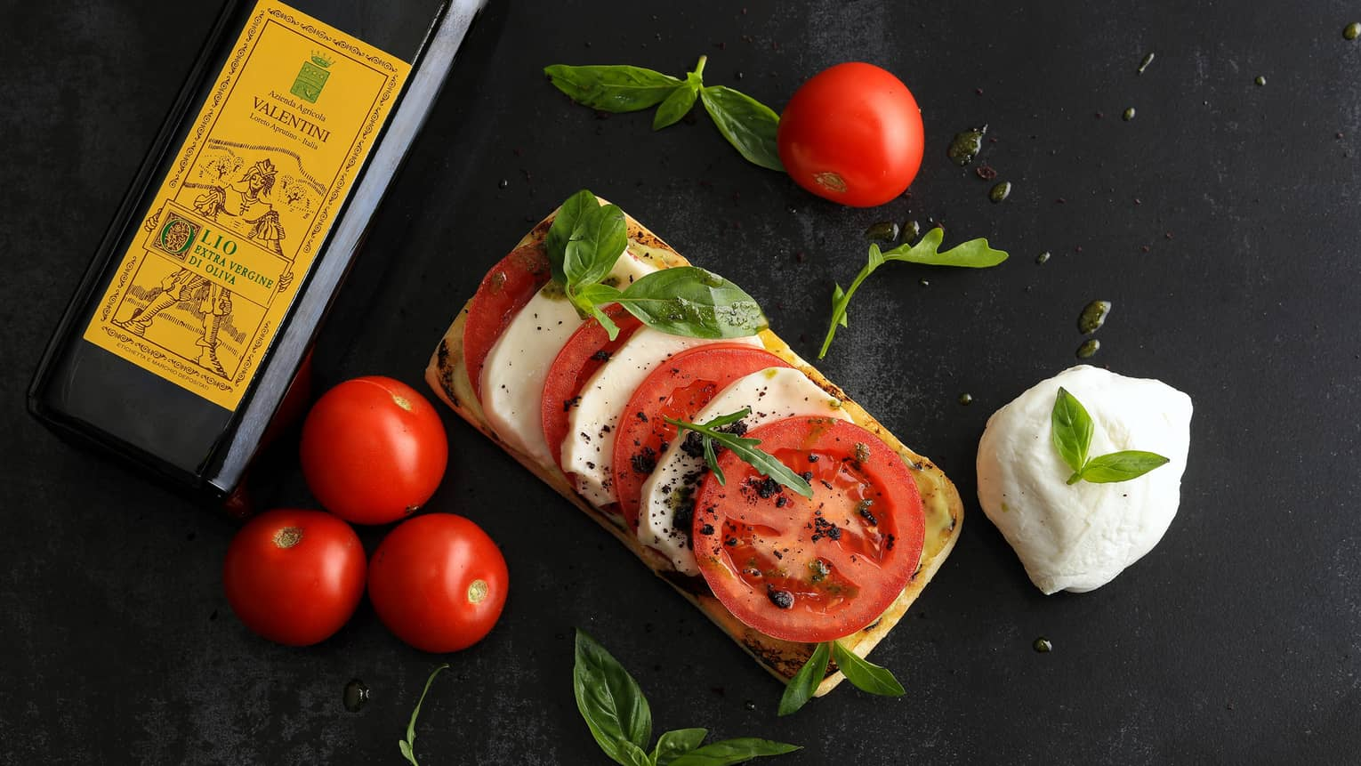 Open-face Tomato & Mozzarella Sandwich garnished with fresh basil, on counter with whole tomatoes