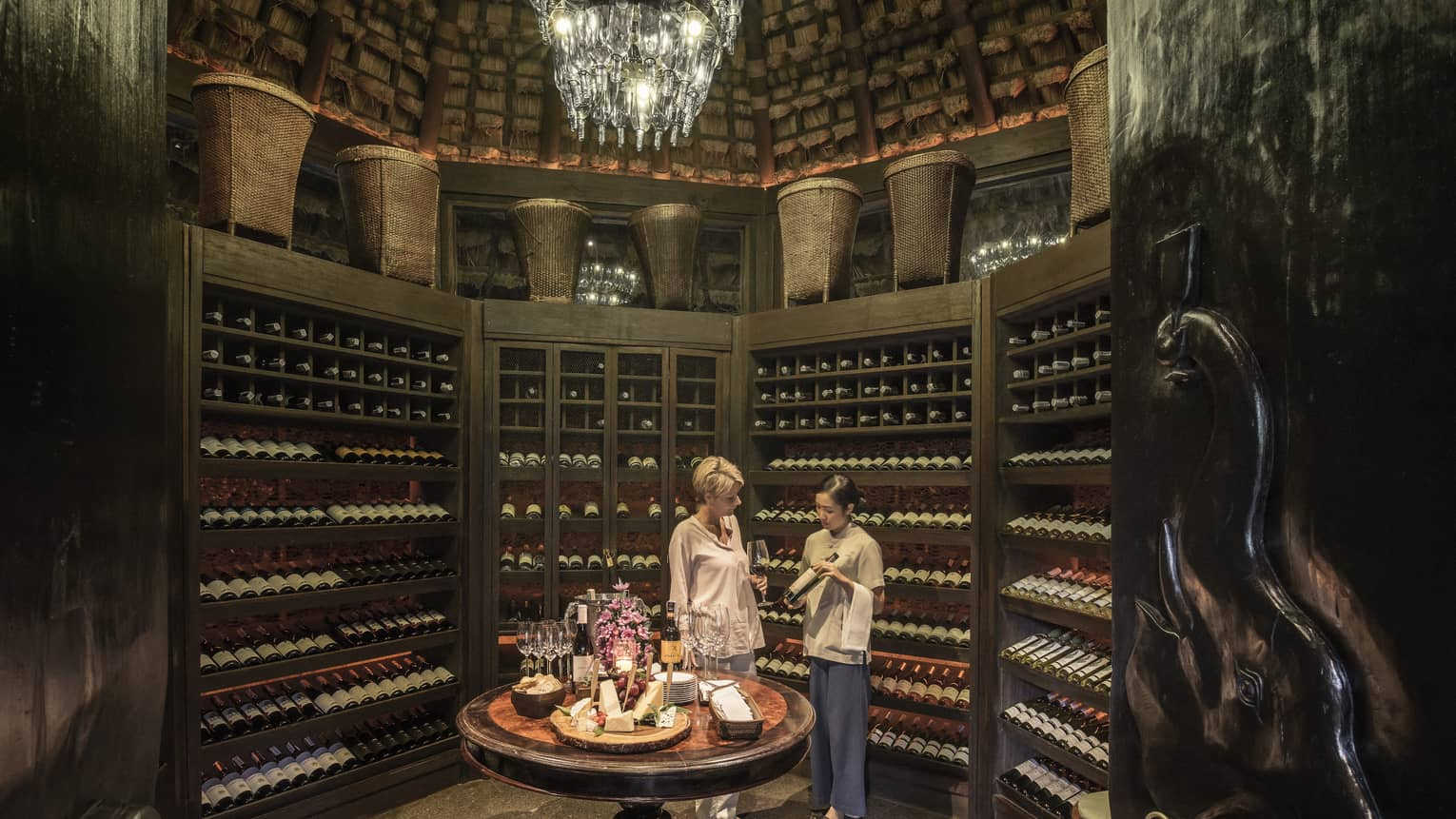 Two people examine wine bottles in Camp Wine Cellar