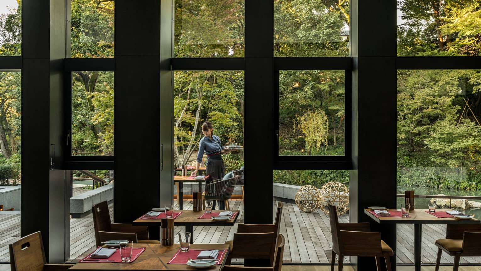 View of Brasserie patio and forest through window, server sets table