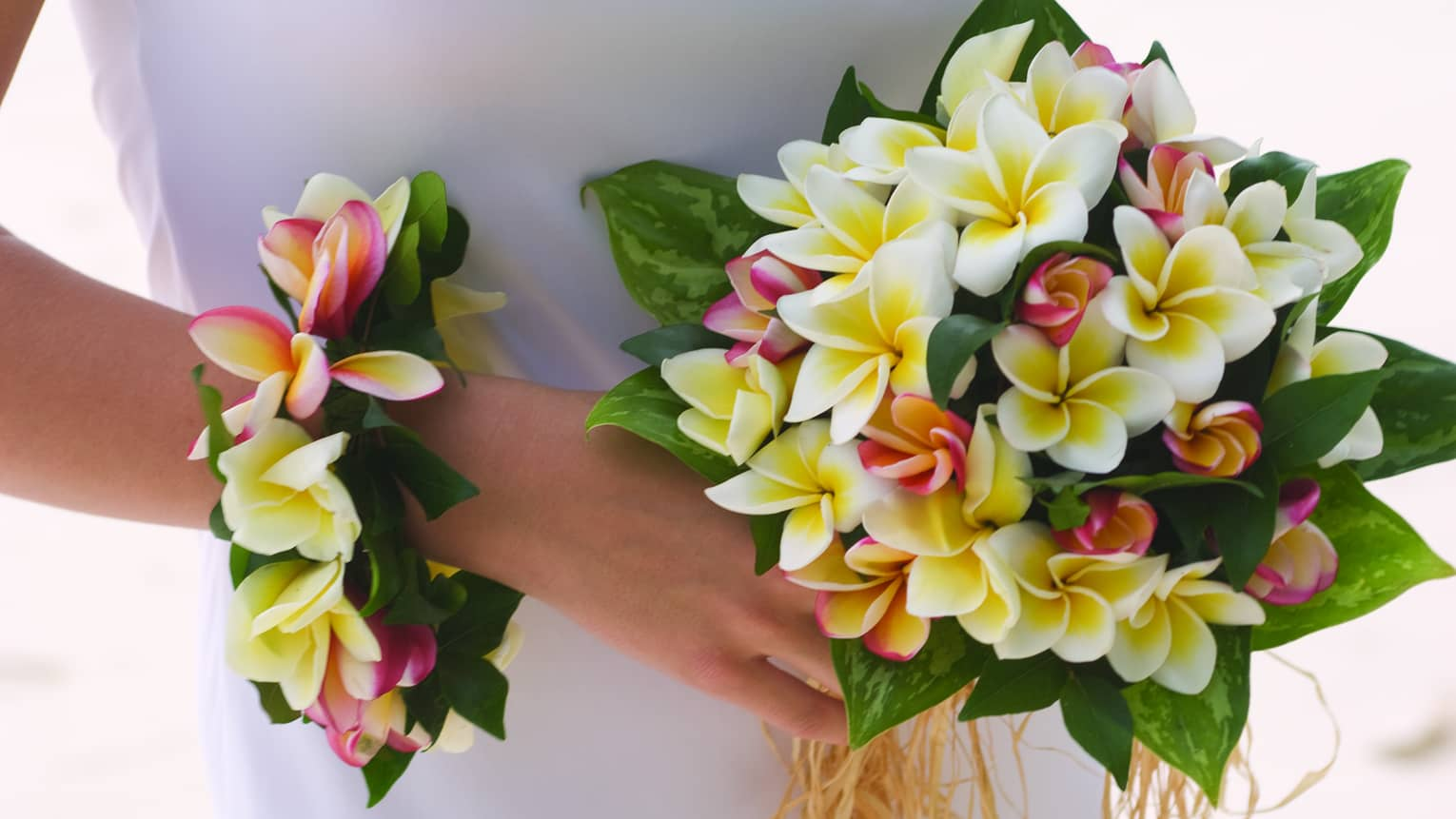 Bride holding wedding bouquet and floral wristband with tropical flowers