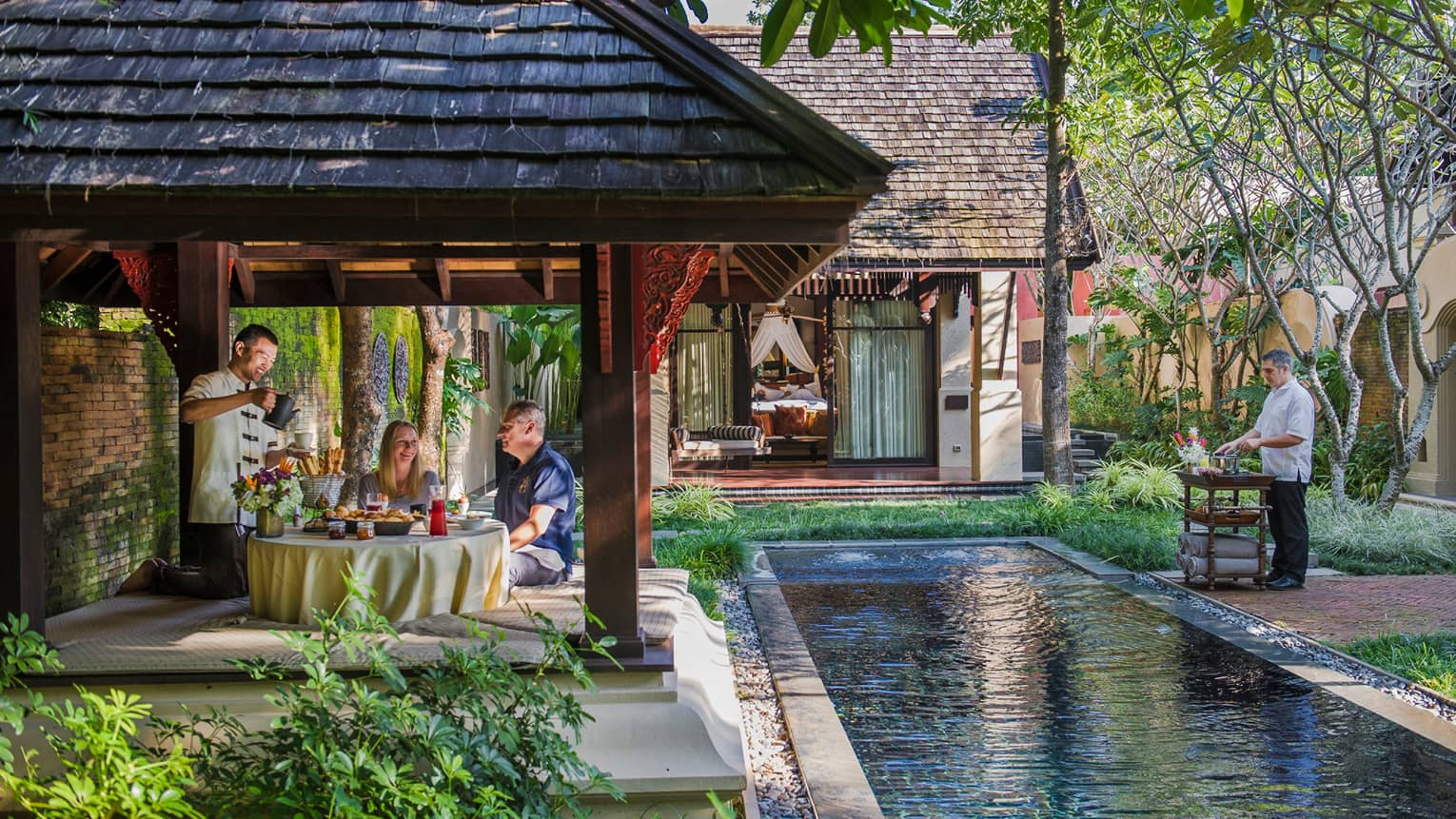 Hotel staff serve couple under dining gazebo by pond