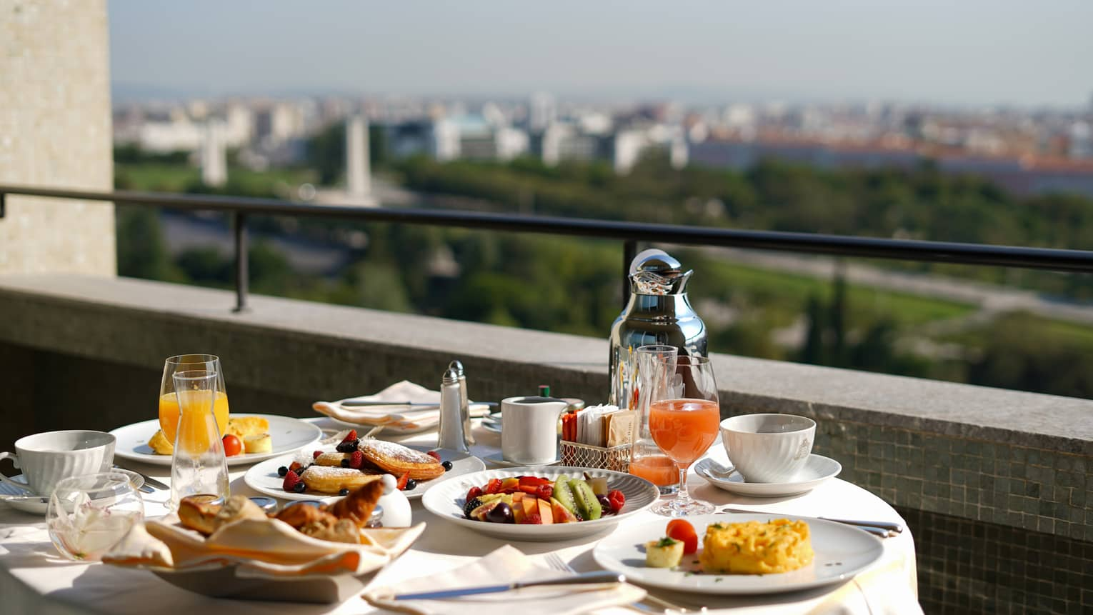 Sunny balcony breakfast dining table with fresh fruit plates, juice, coffee
