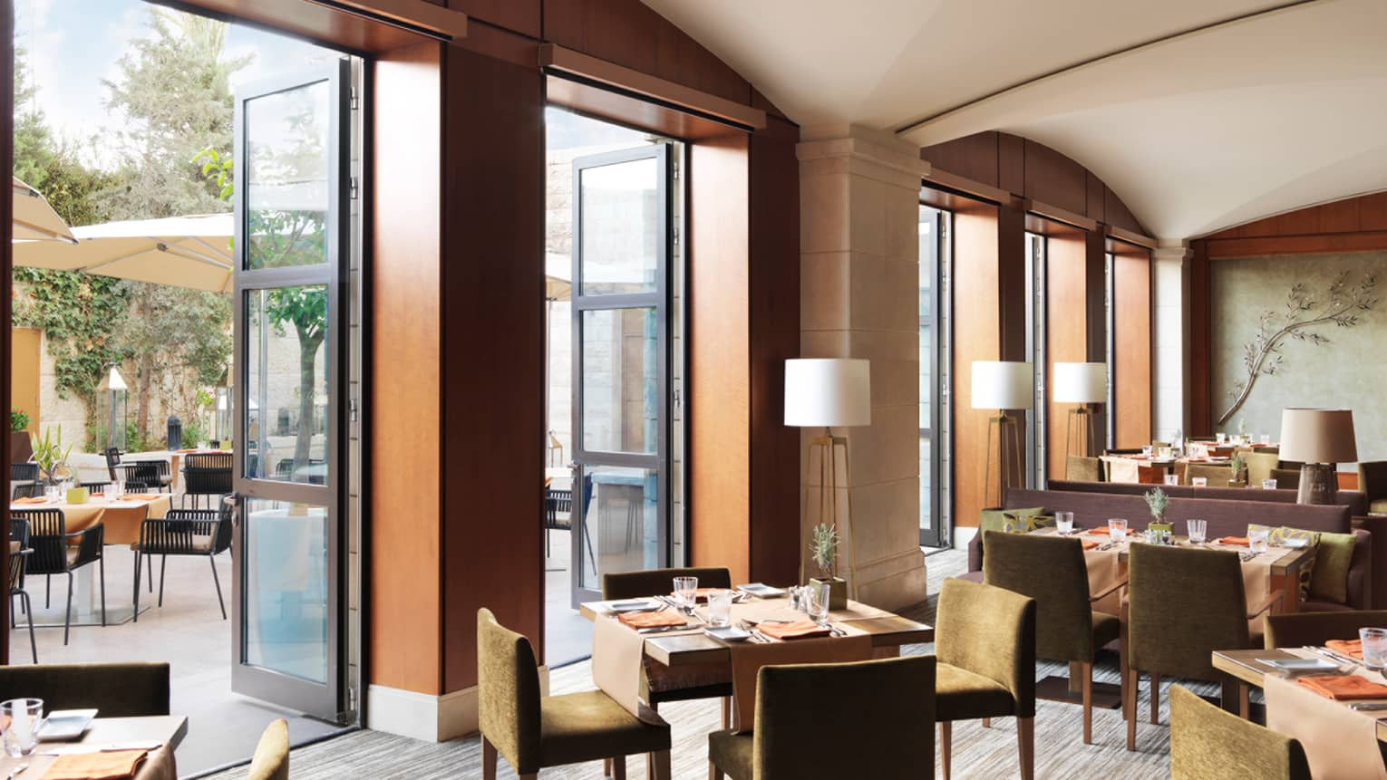 Sunny Olea dining room with tall doors open to patio, tables with brown velvet chairs inside, white lamps