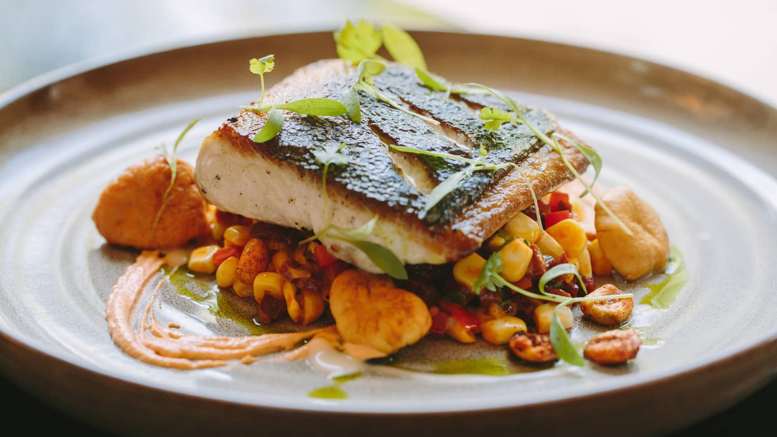 The striped bass, with sweet corn succotash, chorizo, romesco sauce and BBQ hominy