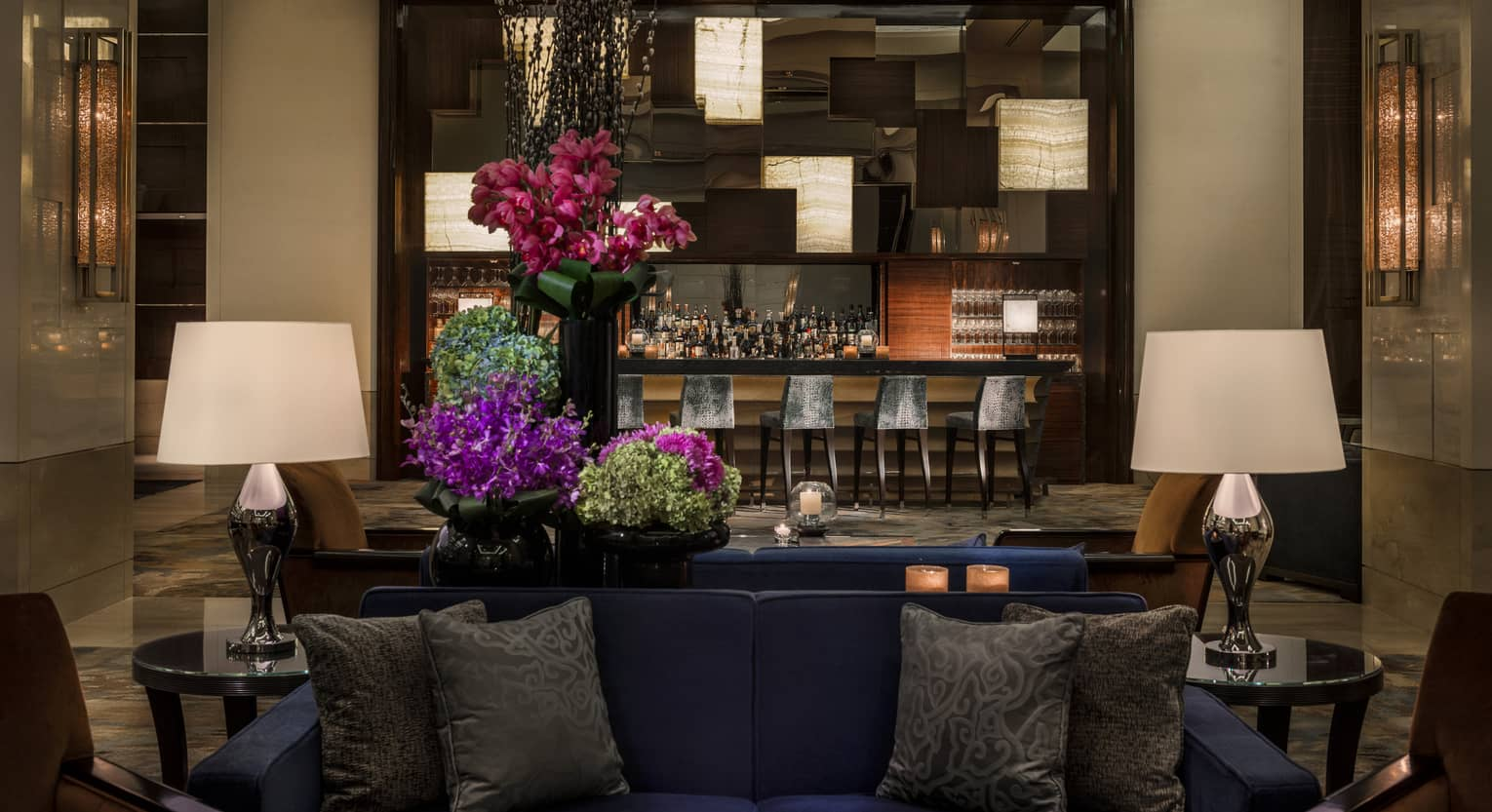 Opus Bar with grey stools behind lounge sofas, purple flowers