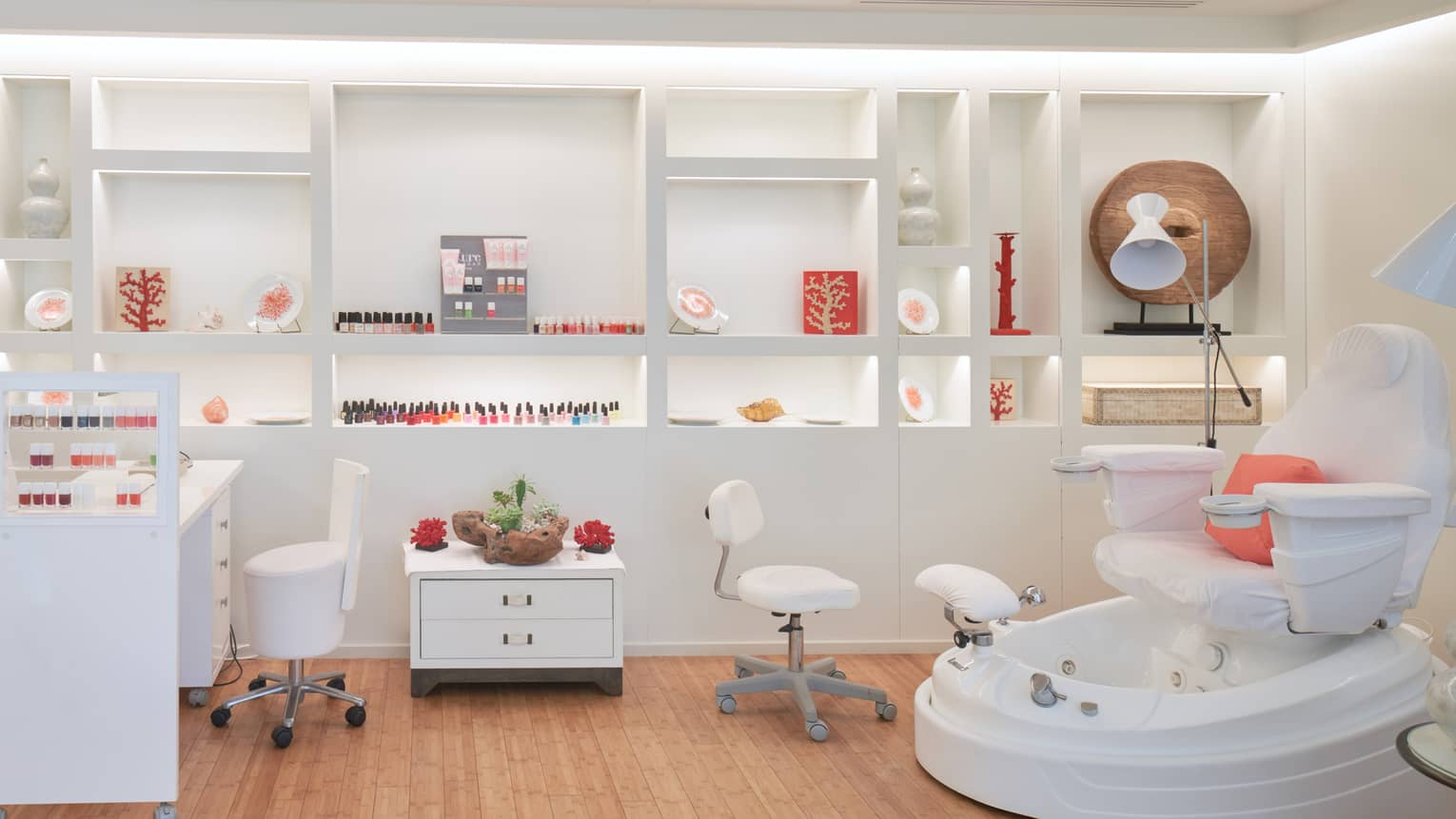 Spa nail bar with manicure station and polish, white wheeled stools, spa pedicure chair, shelving in back