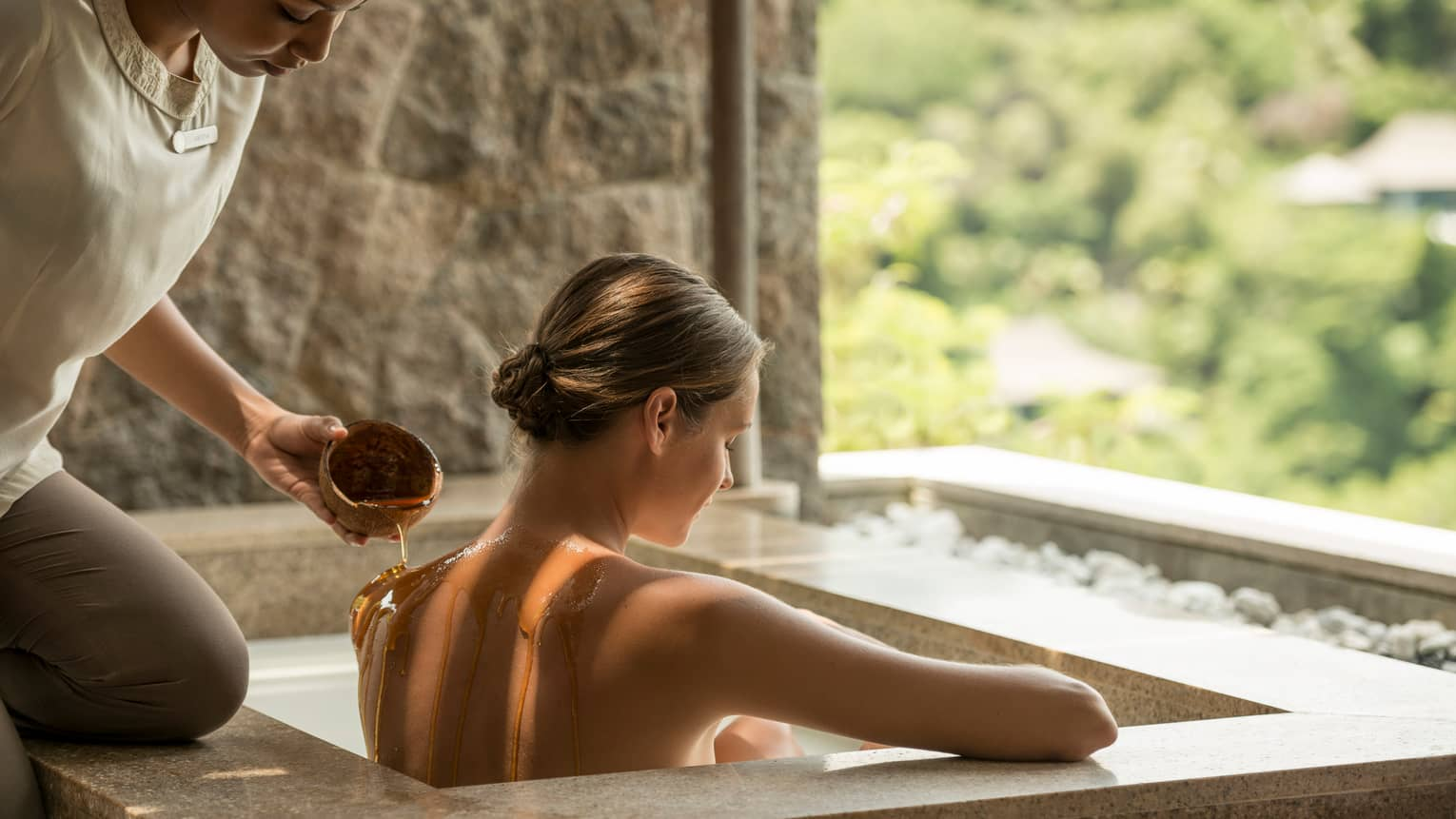 Spa attendant pours hot oil on woman's bare shoulders as she sits in rectangular tub