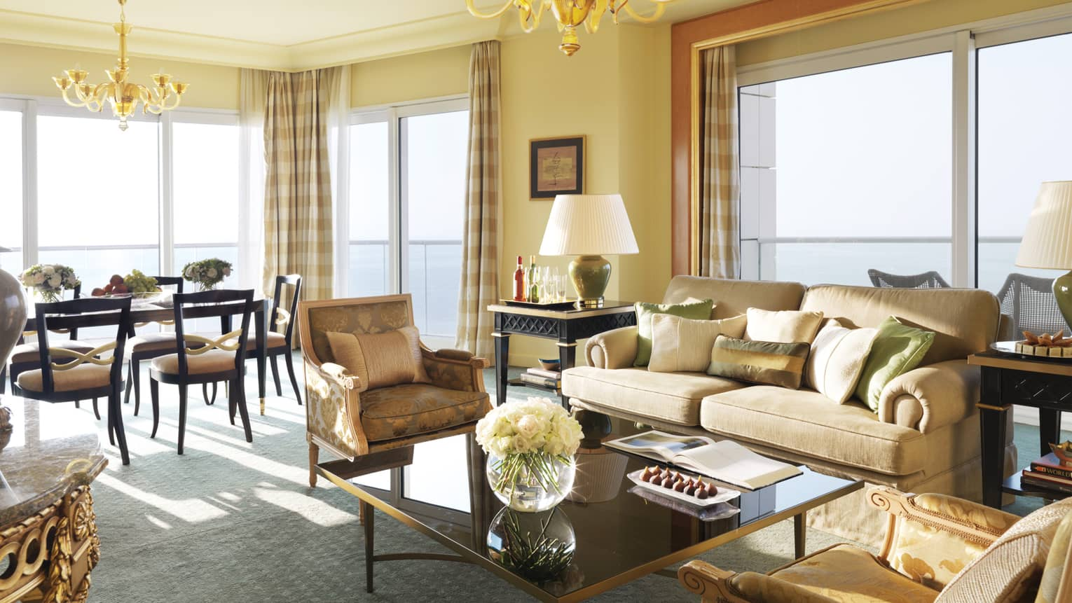Premier Suite living room, beige sofa with green-and-gold pillows and elegant accent chairs, dining room in background