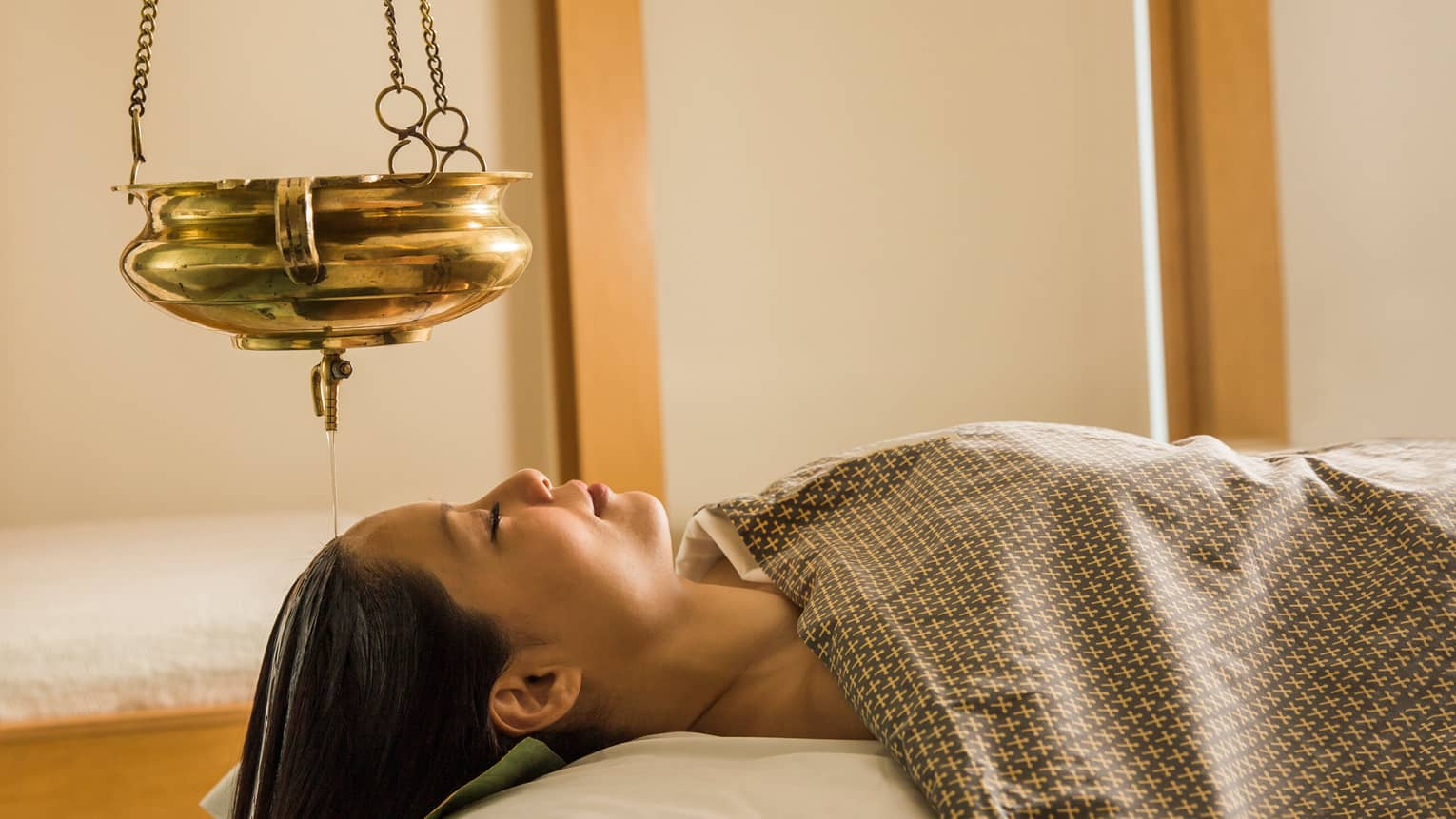 Woman lies face-up on massage table under blanket, eyes closed, gold lamp hanging above head